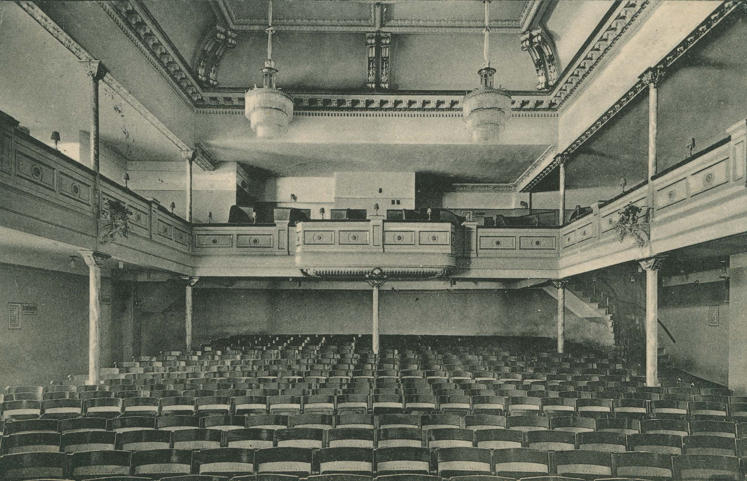 Black and white photo: auditorium with balustrade and two chandeliers