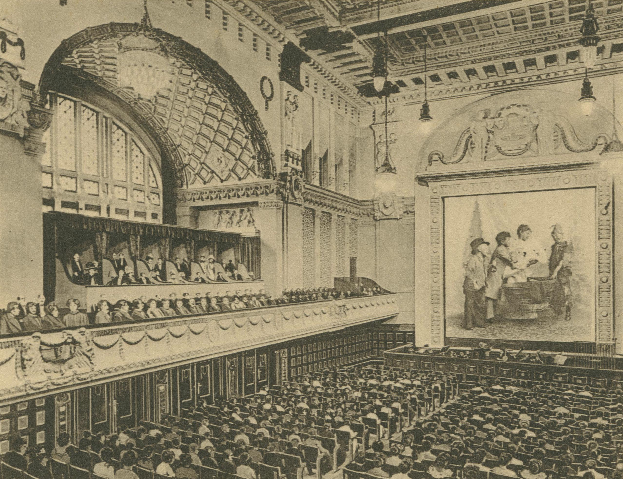 Auditorium with guests facing the screen with balustrade and paneled ceiling.