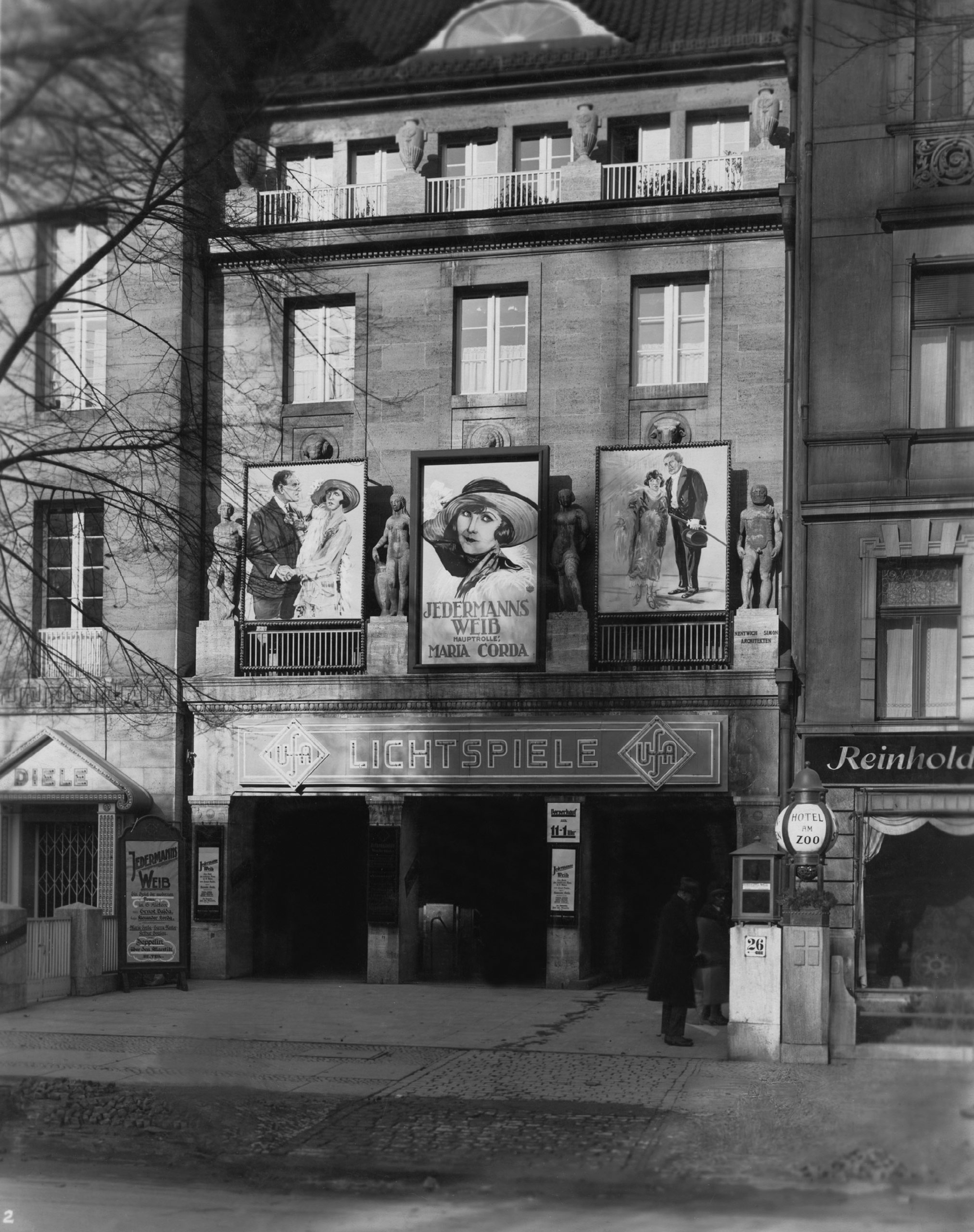 Black and white photo: the front of the cinema with film posters