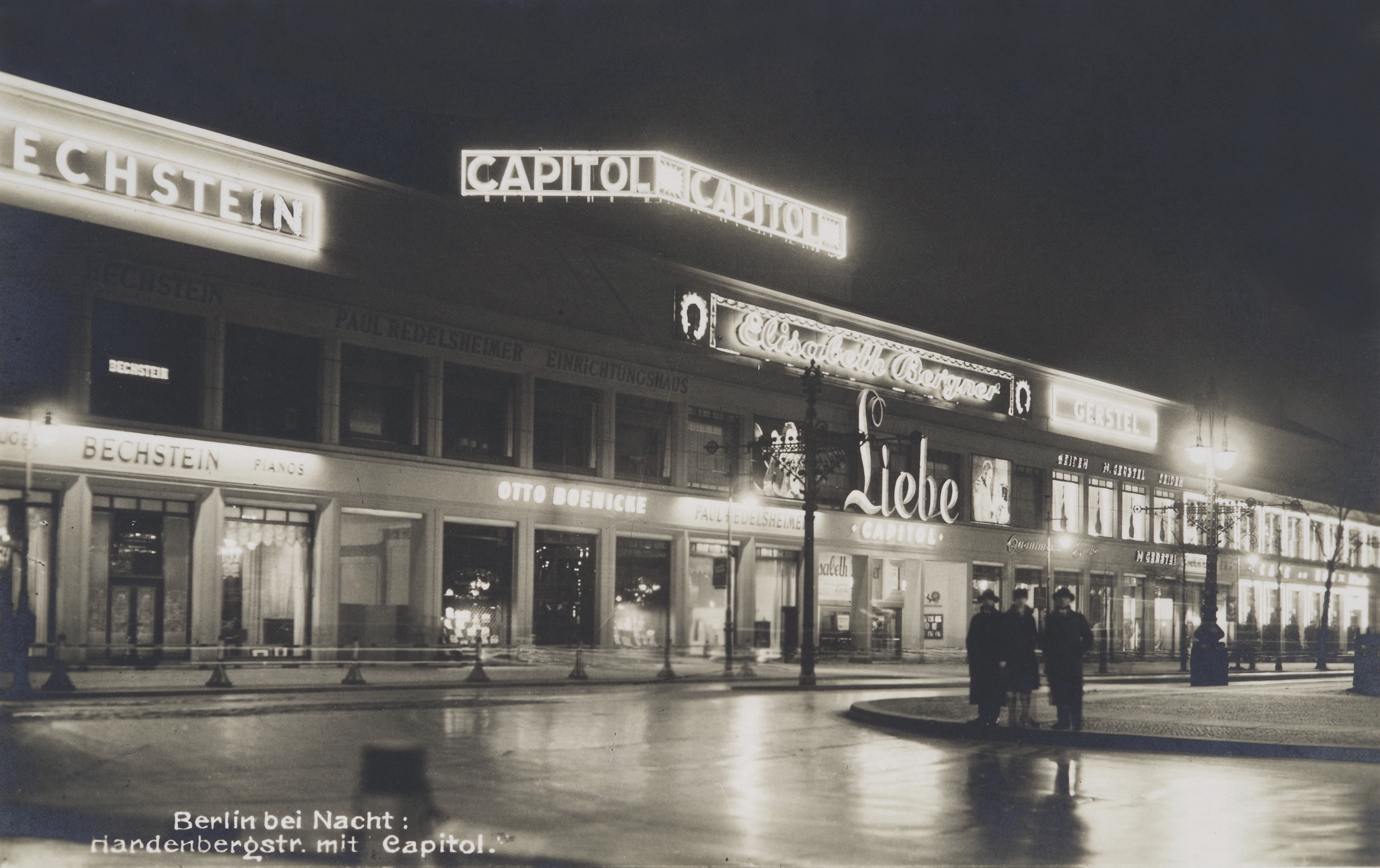 Black and white photo: front of the cinema with illuminated advertisements