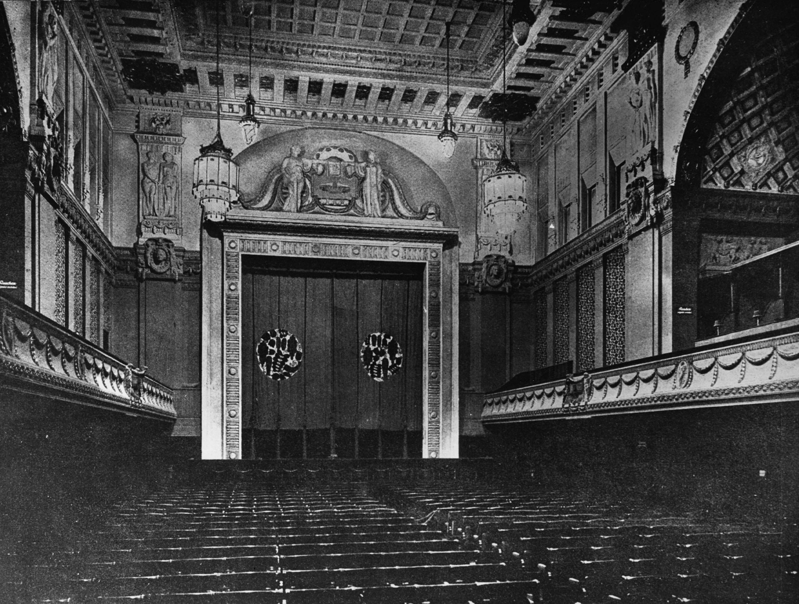 Black and white photo of the auditorium with paneled ceiling facing the screen