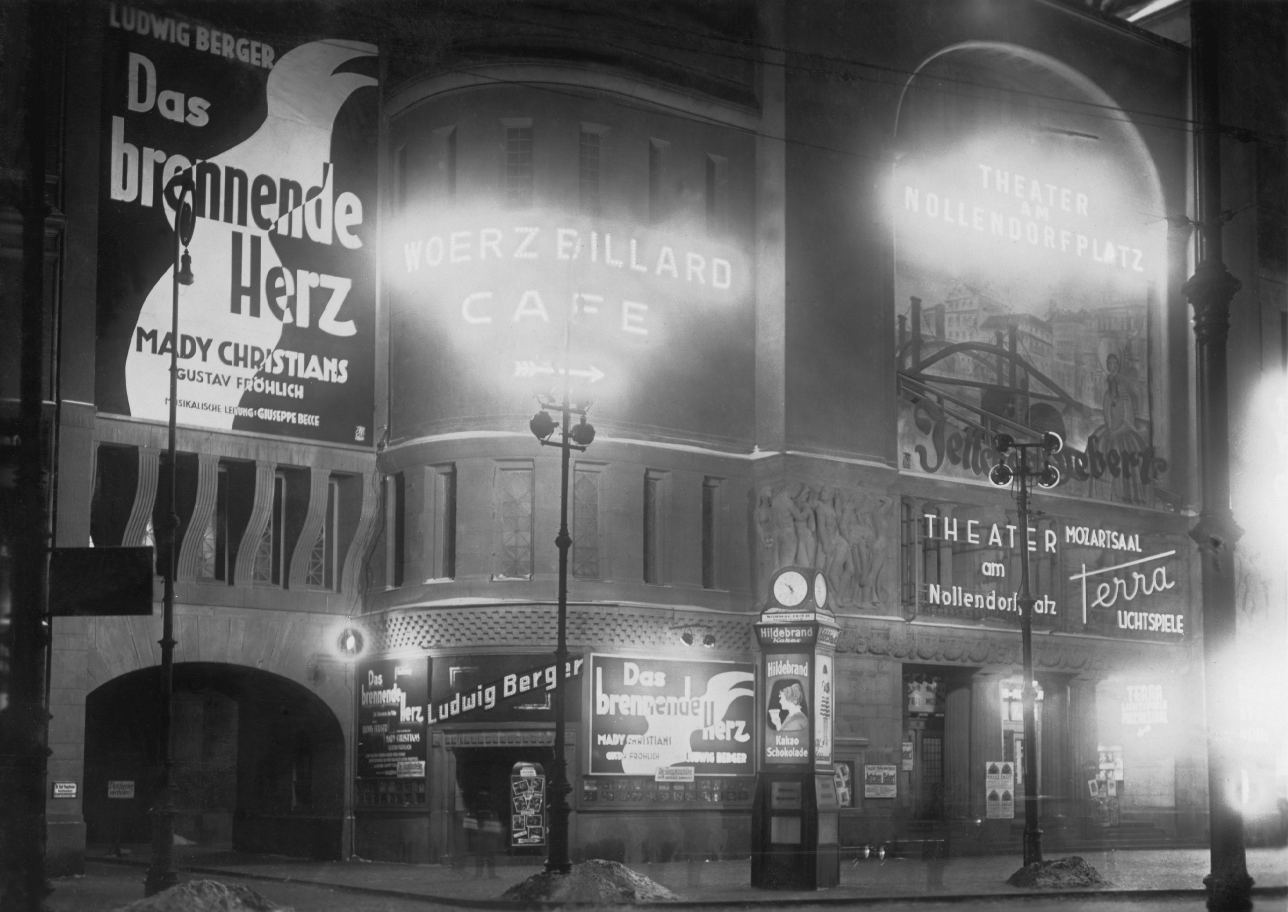 Black and white photo: the front of the cinema with illuminated advertising and film posters for Das brennende Herz