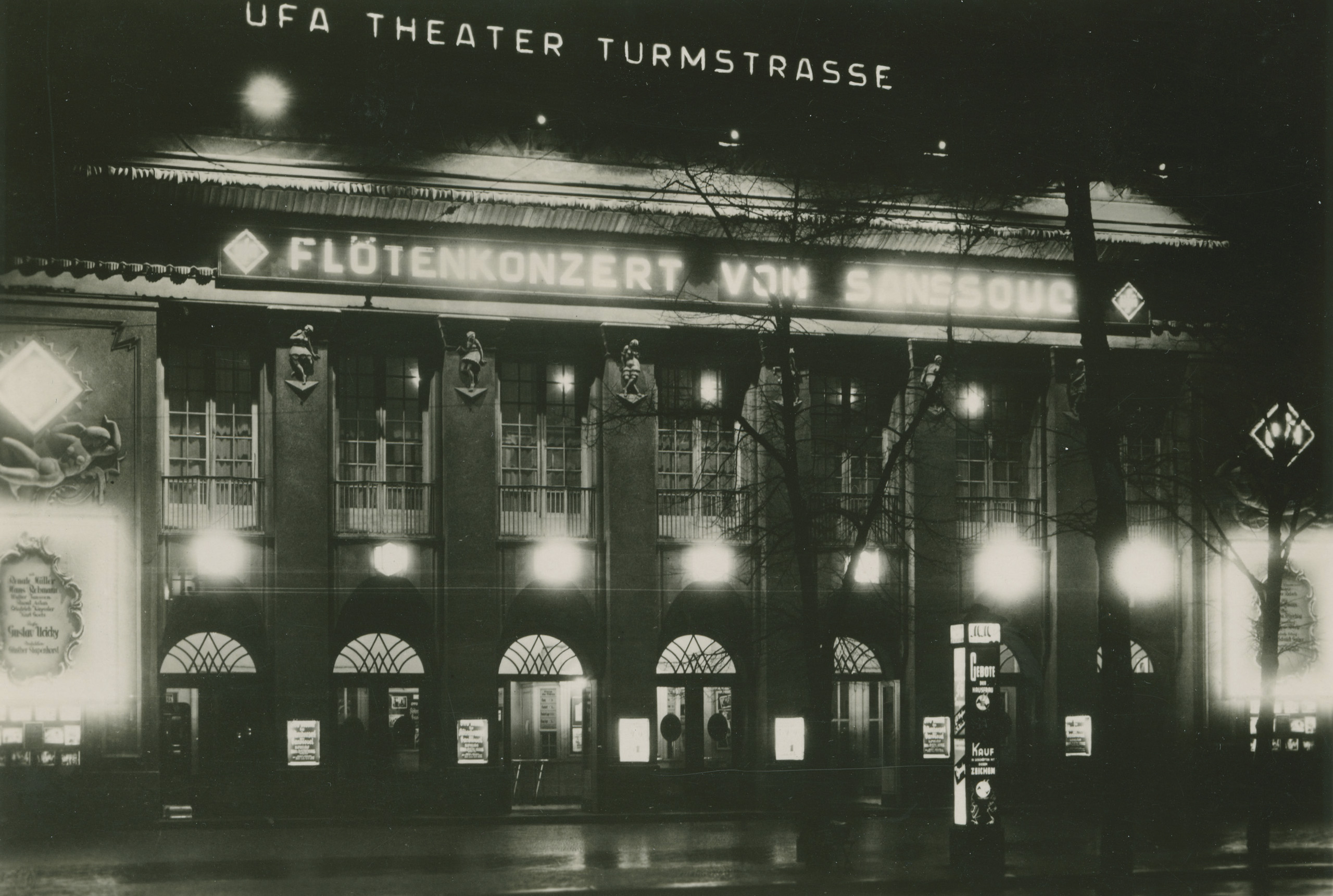 Black and white photo of the cinema façade at night with illuminated advertisements