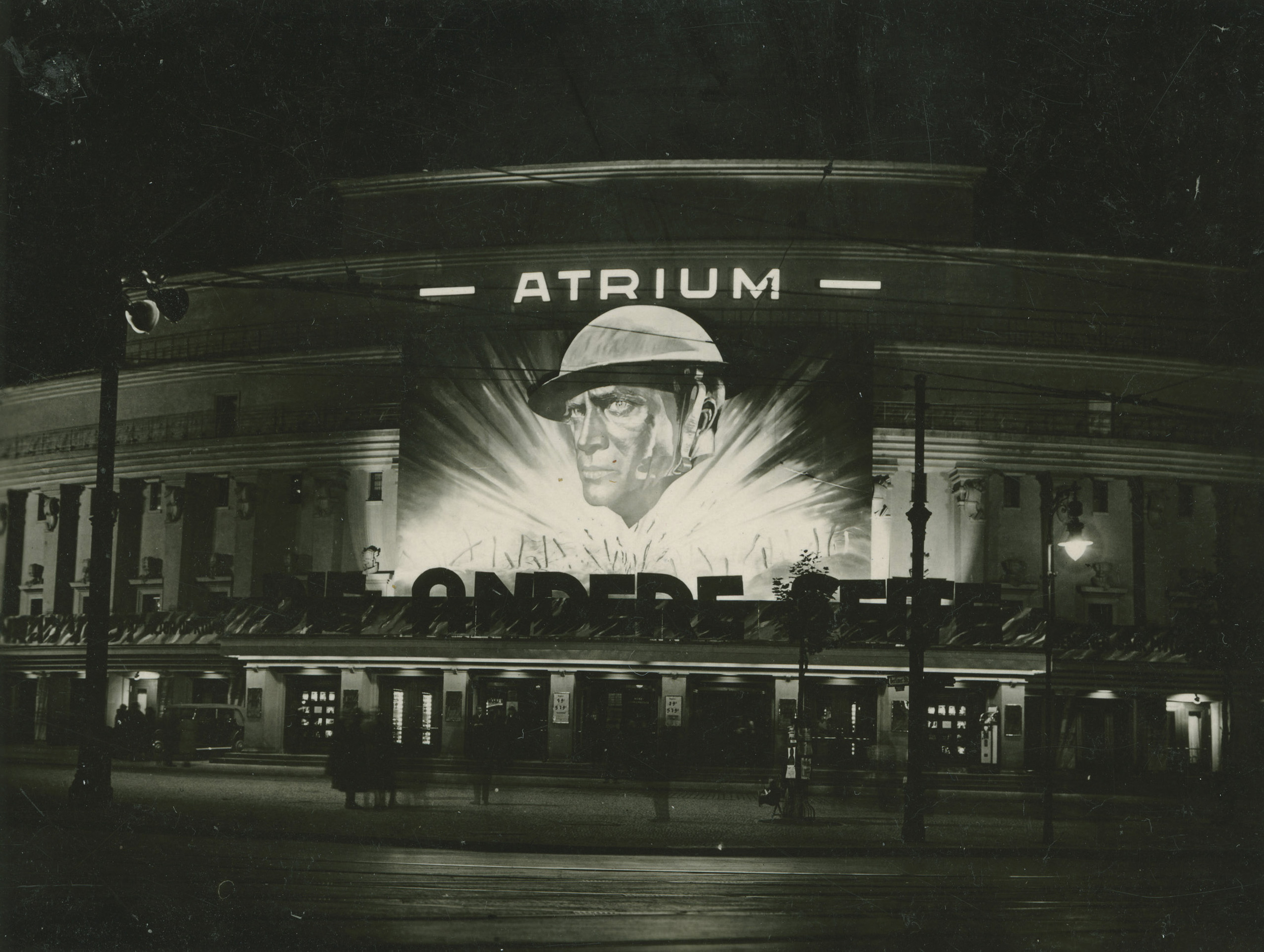 Black and white photo of the cinema façade at night with advertisements for a movie about soldiers