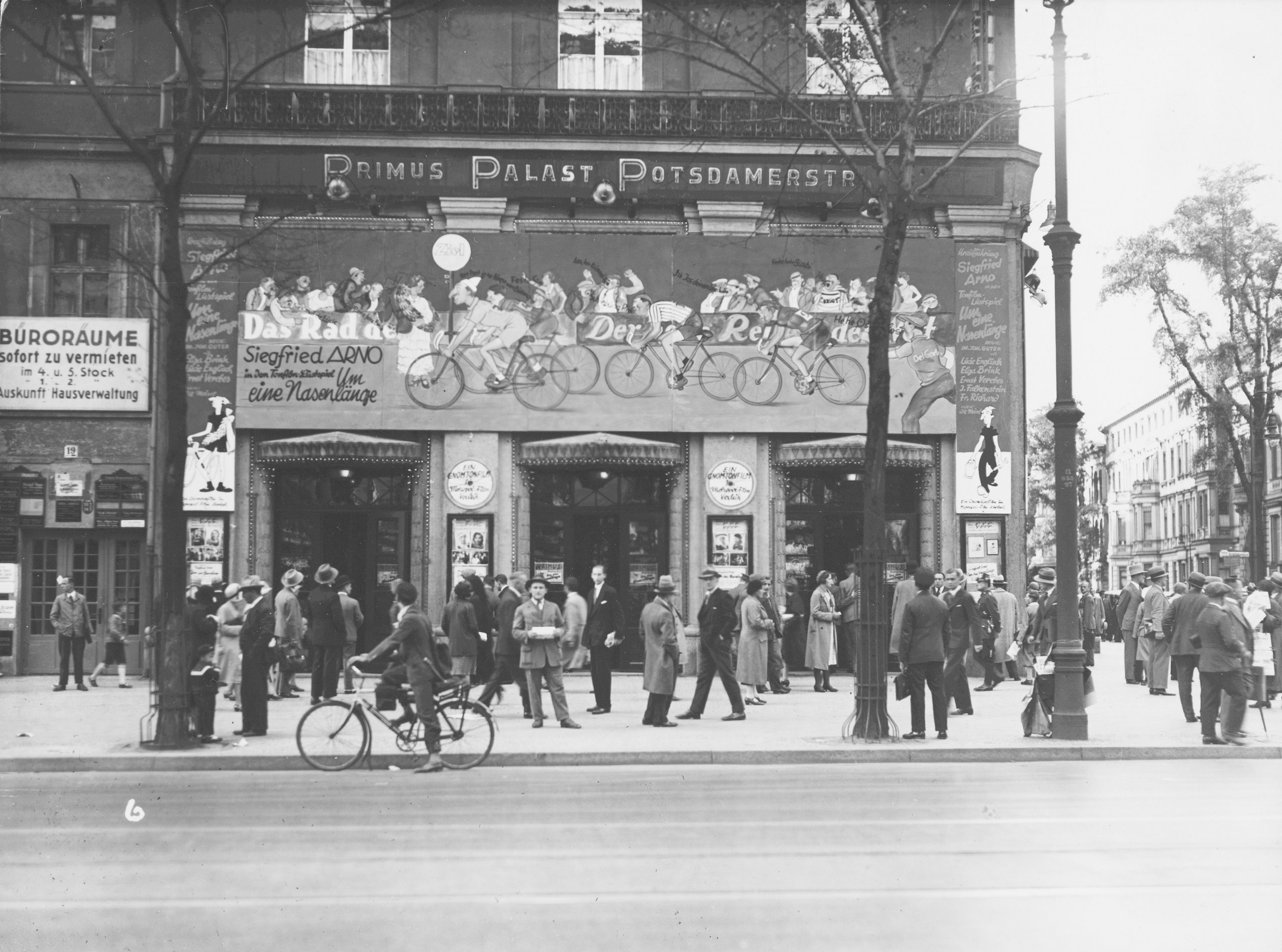 Black and white photo of people queuing outside of the cinema and advertisements for the cycling film Um eine Nasenlänge