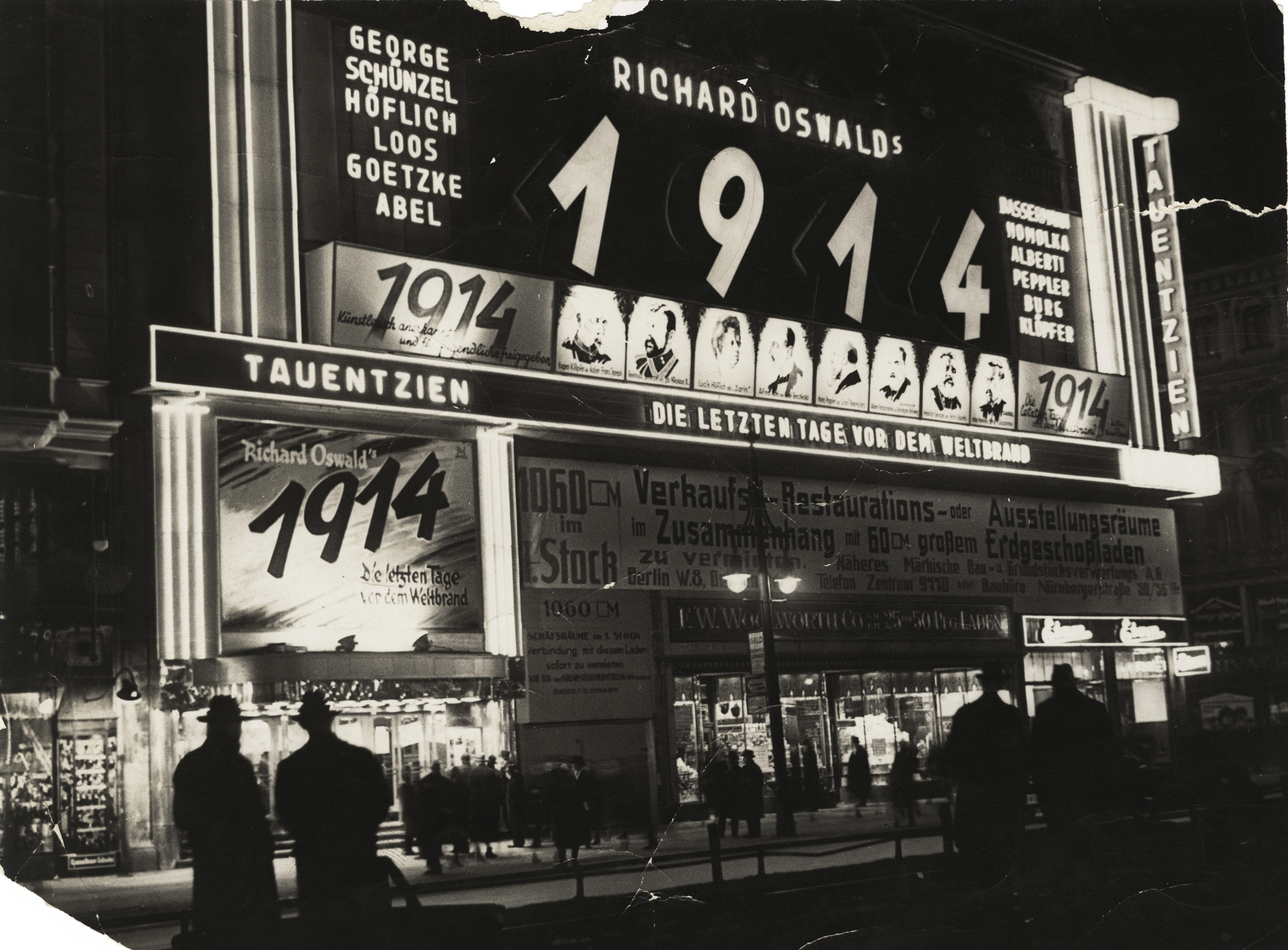 Black and white photo of the façade at night with illuminated advertisements and posters for Richard Oswald's film 1914