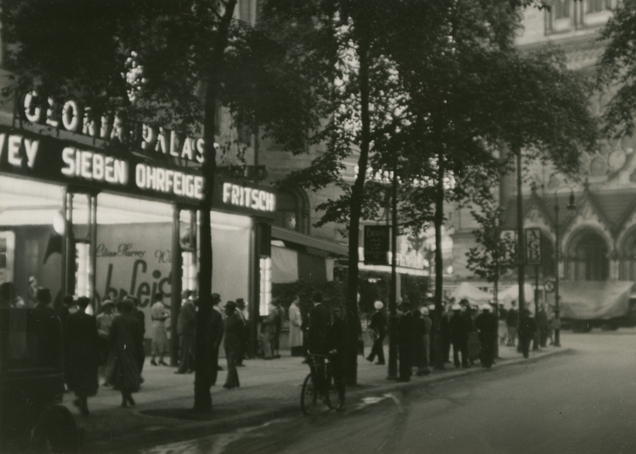 Black and white photo: cinema with illuminated advertisements and people queuing to go inside