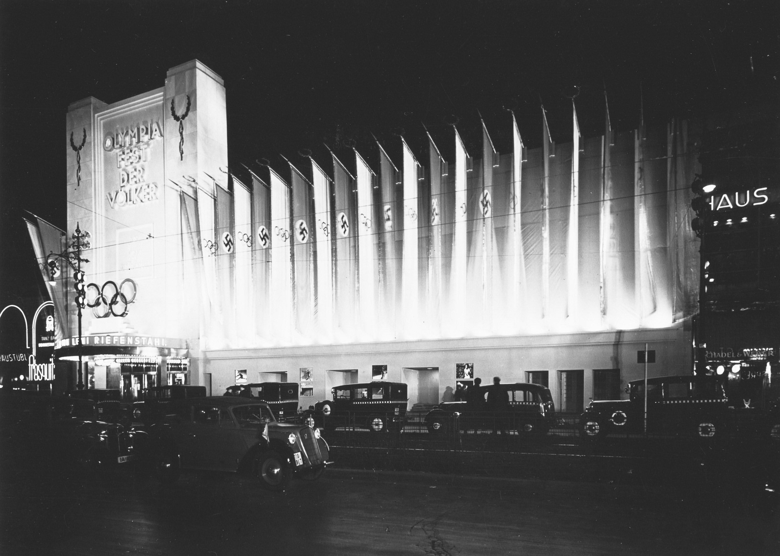 Black and white photo: illuminated flags of the German Reich in front of a cinema building at night