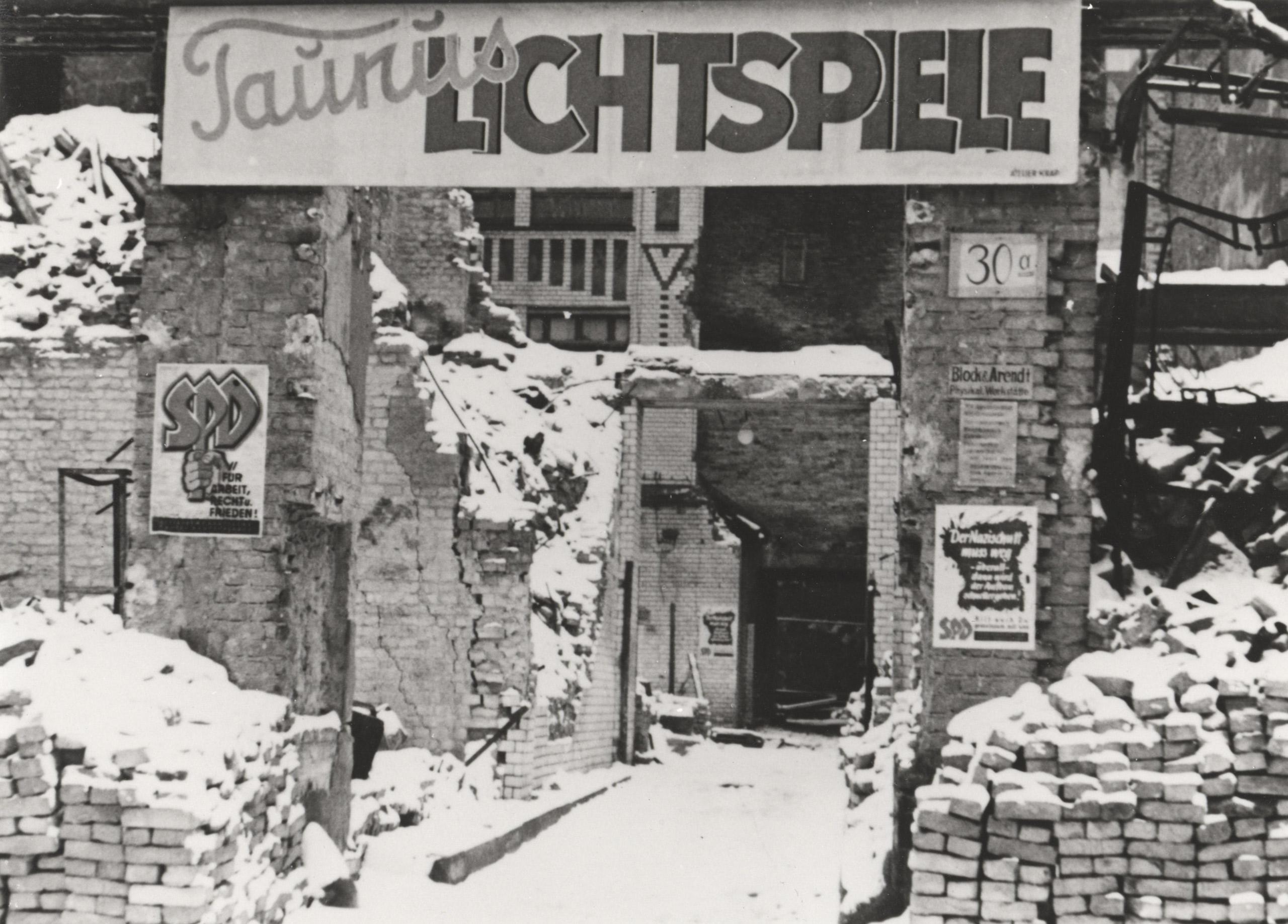 Schwarz-Weiß-Foto: verschneite Ziegel vorm Kinoeingang
