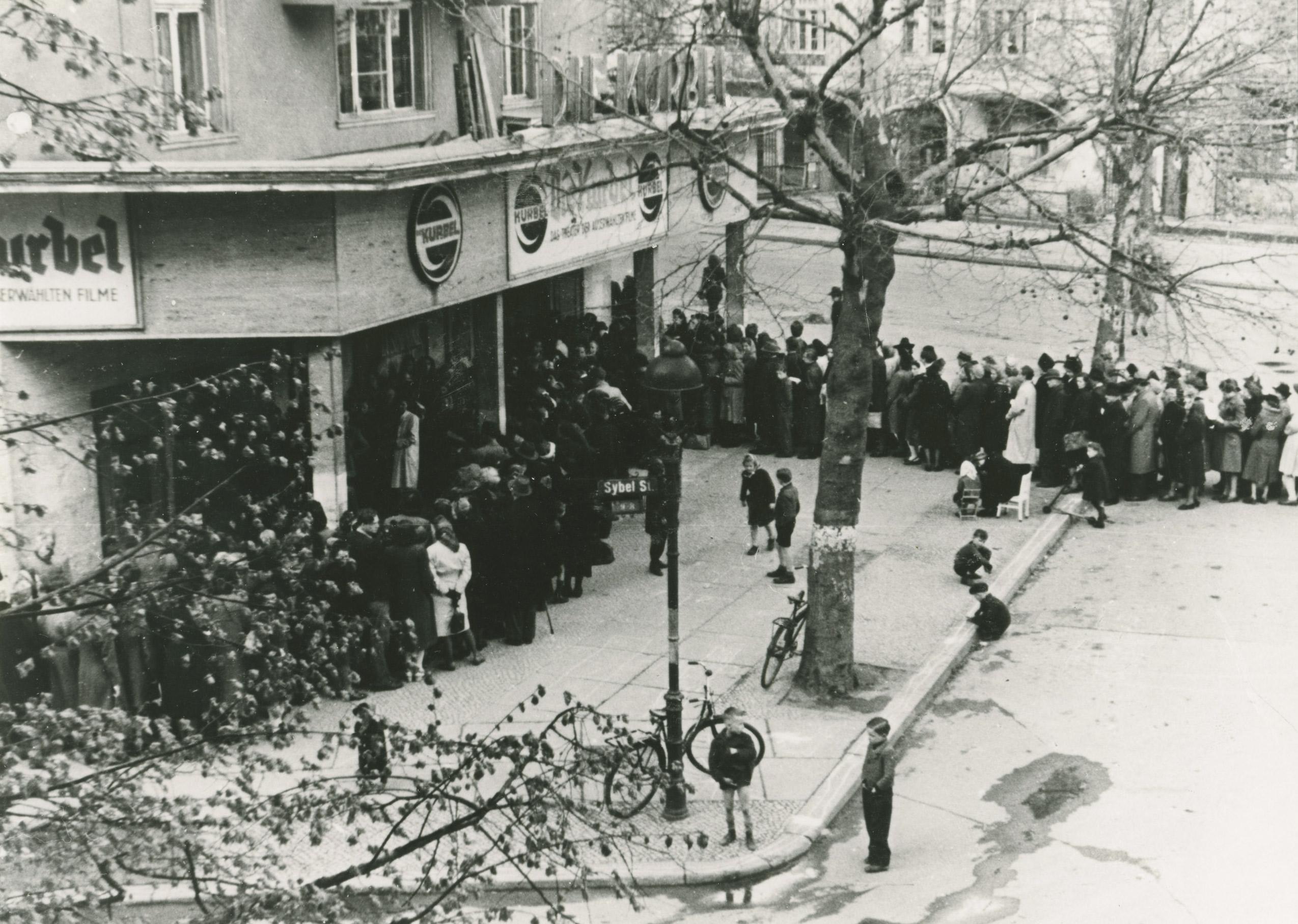 Schwarz-Weiß-Foto: lange Menschenschlage vor dem Kino
