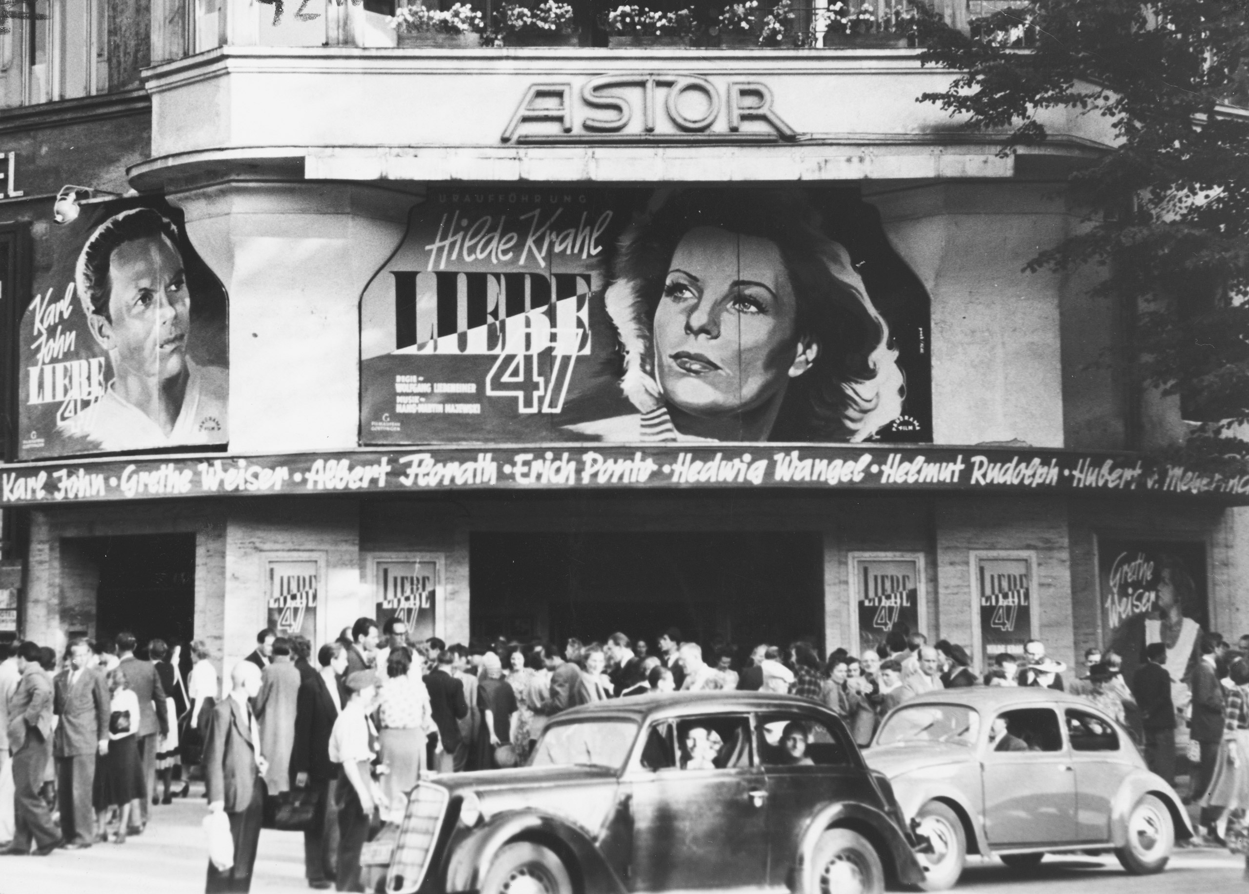 Black and white photo: people outside the cinema with posters for the film Liebe 47 (directed by Wolfgang Liebeneiner)
