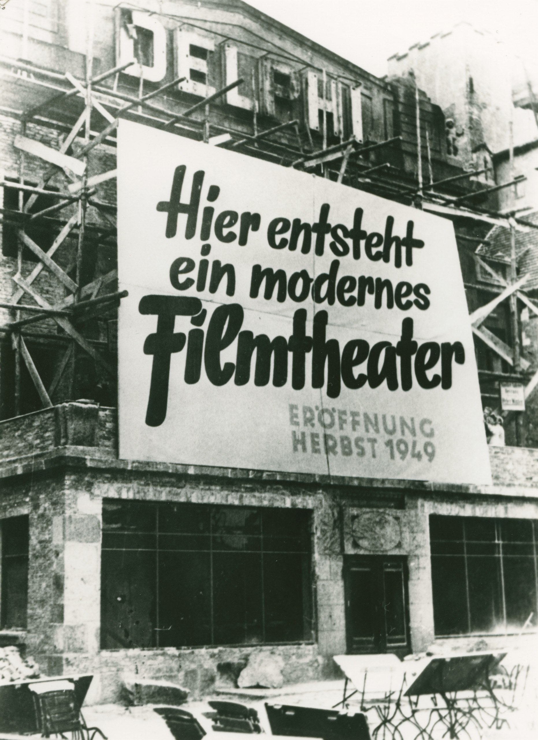 "Black and white photo:scaffolding outside the building with a banner saying ""A modern cinema is being built here"""