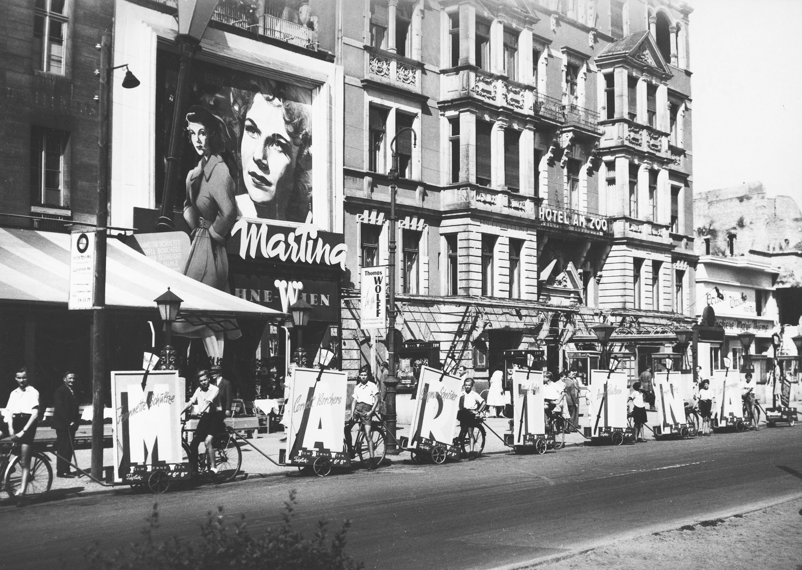 Black and white photo: a platoon of cyclists with advertisements for the film Martina in front of the cinema