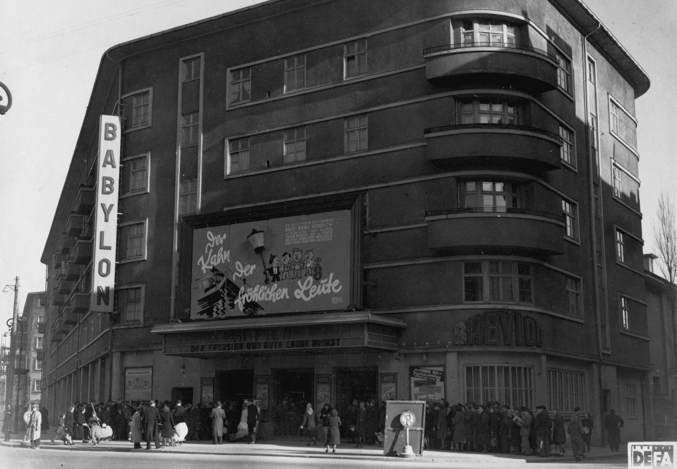 Black and white photo: people outside the box office of the cinema