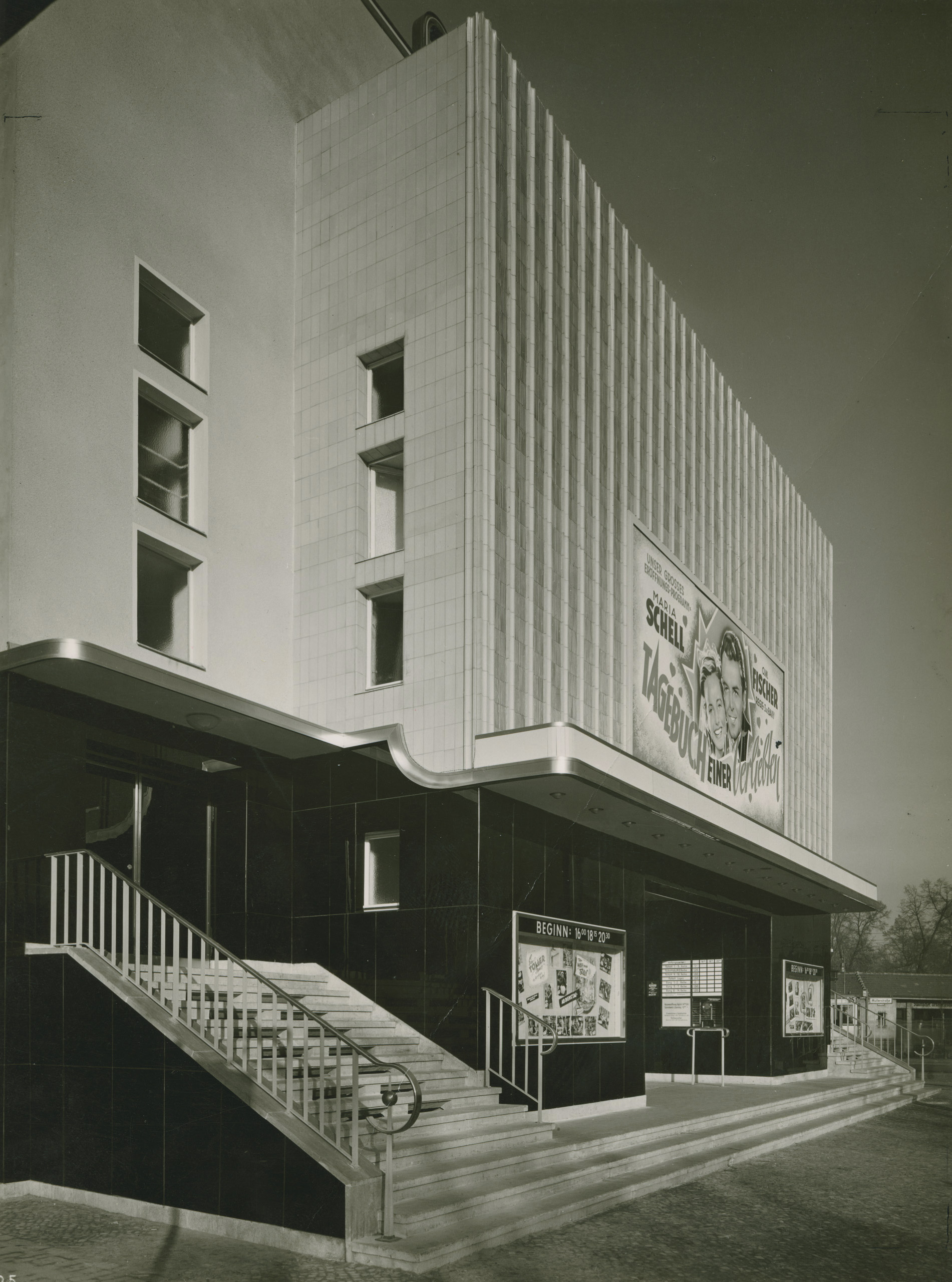 Black and white photo: diagonal view of the façade with film advertisements