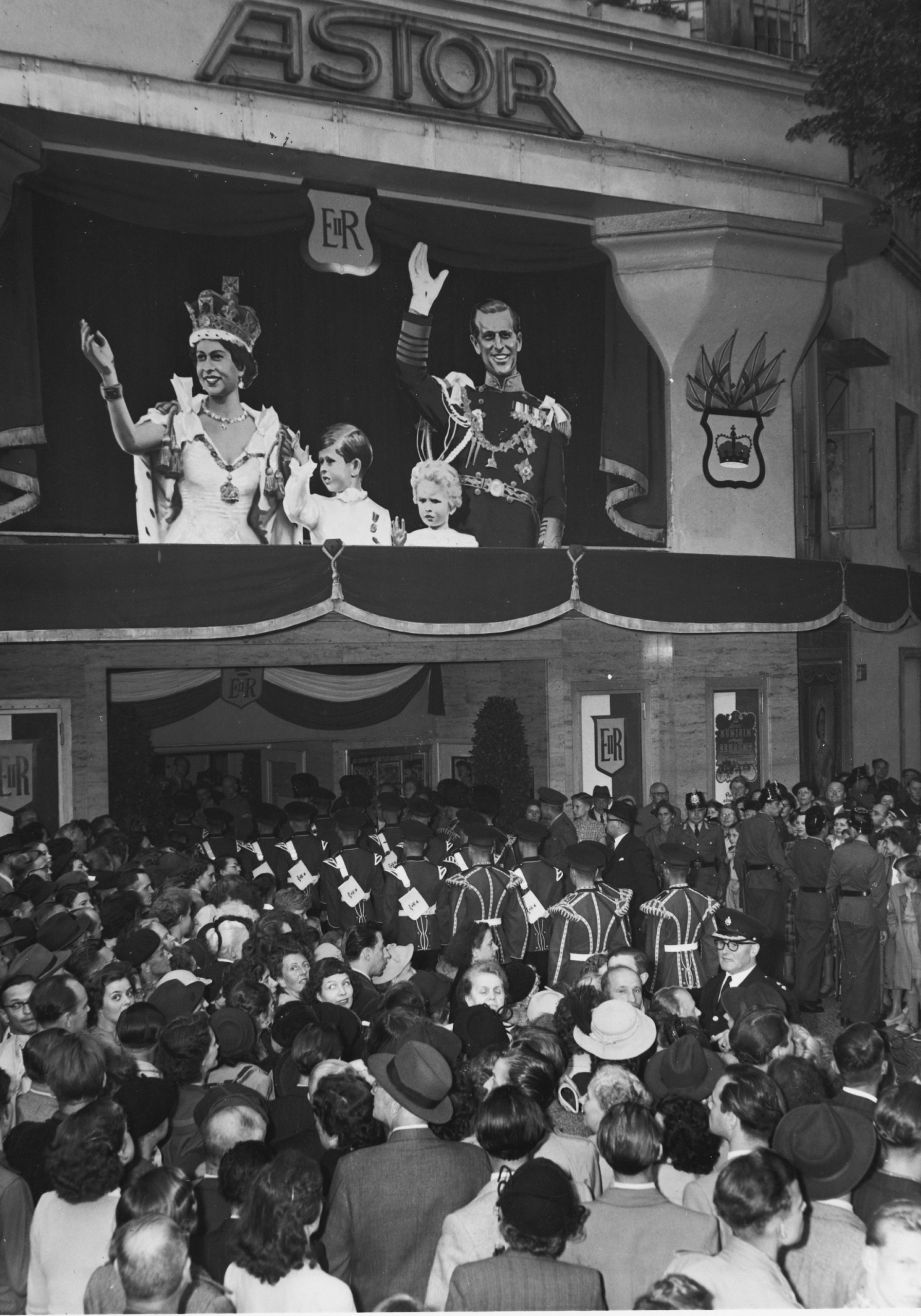 Black and white photo: a crowd gathered outside the cinema with a poster of the royal family of the UK on the façade