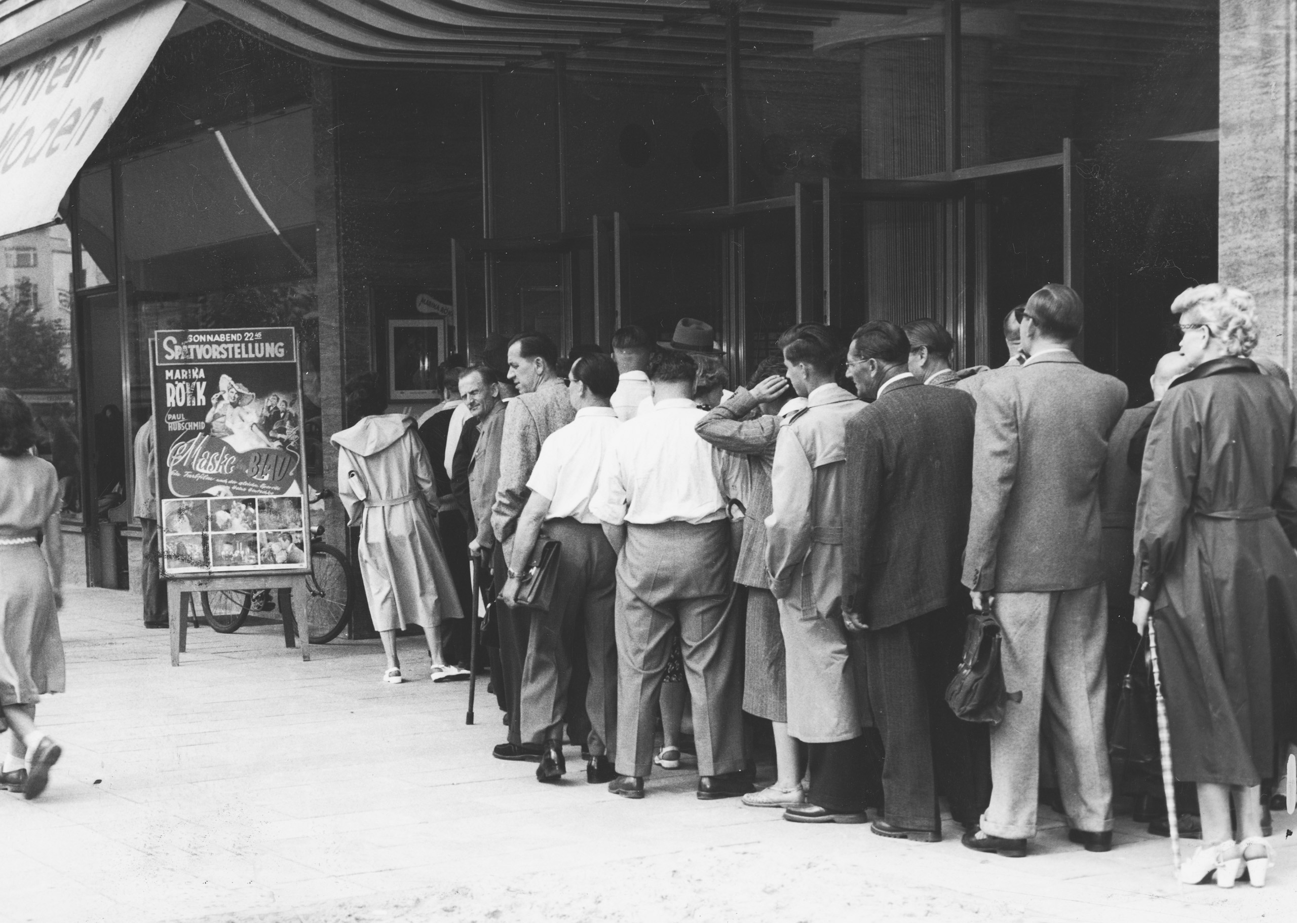 Black and white photo: people queuing outside the cinema