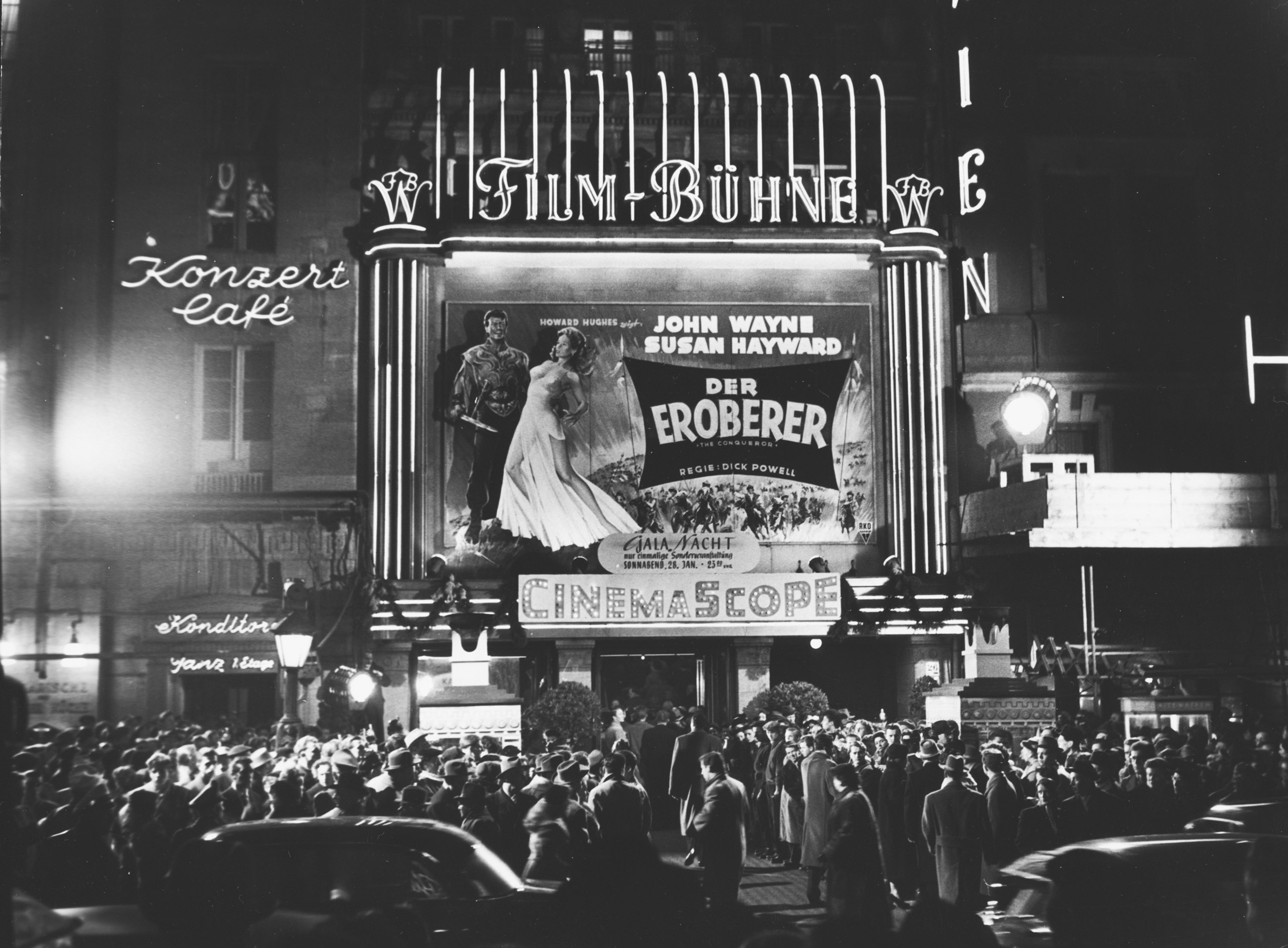 Black and white photo: cinema façade at night with illuminated advertisements, posters for Der Eroberer (directed by Dick Powell) and a crowd of people