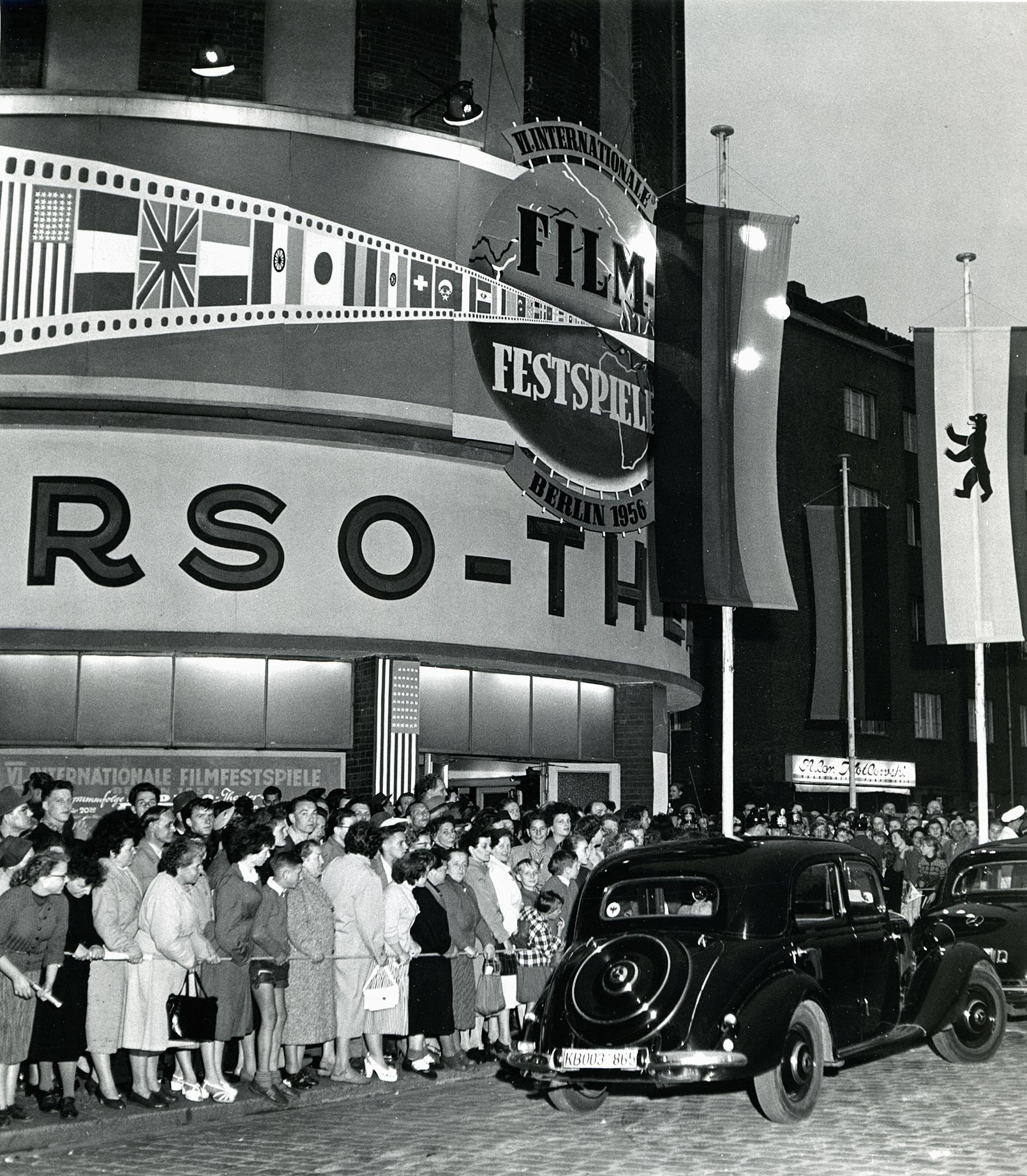 Black and white photo of a crowd in front of the cinema
