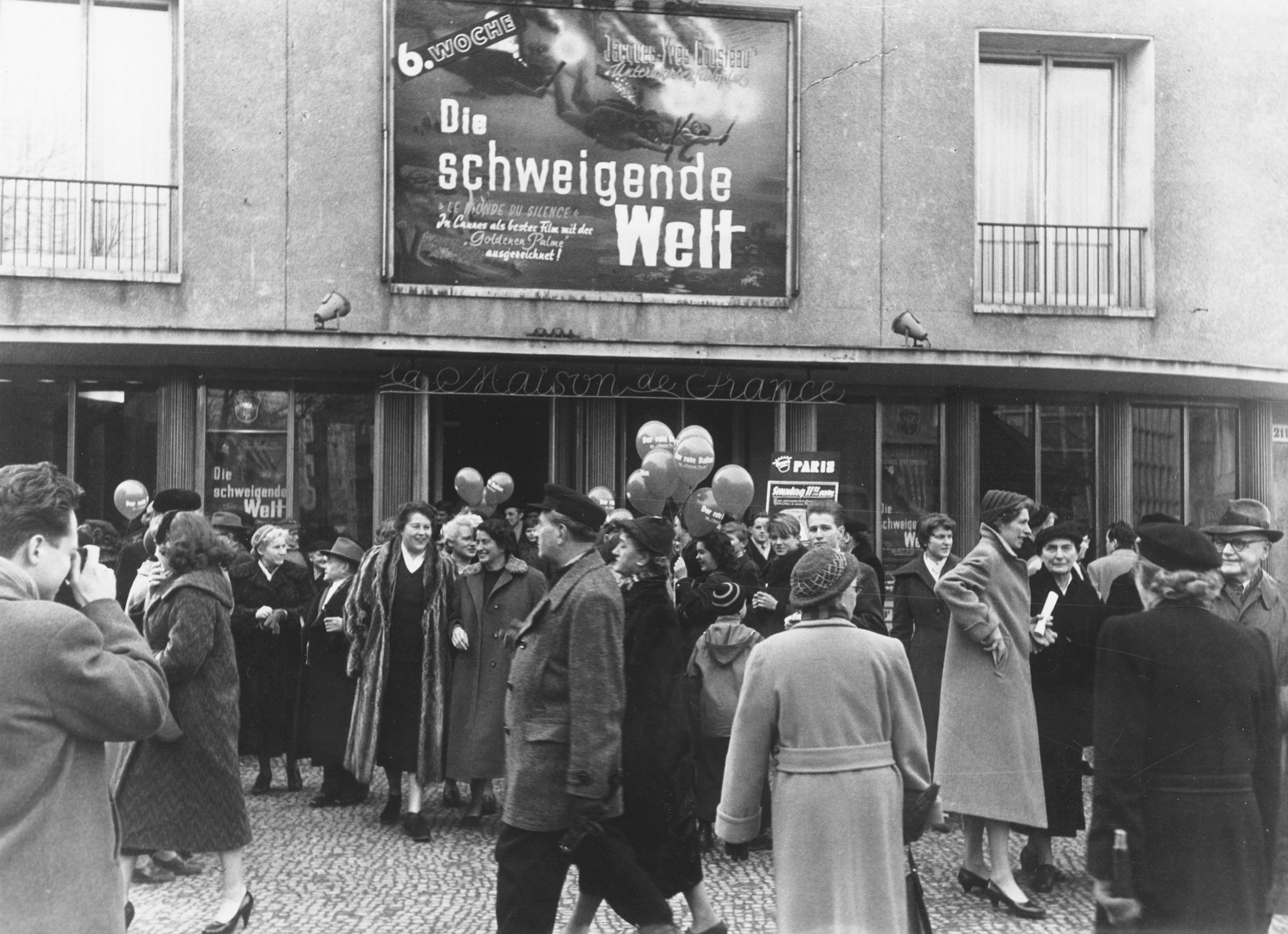 Black and white photo: a group of people outside the entrance