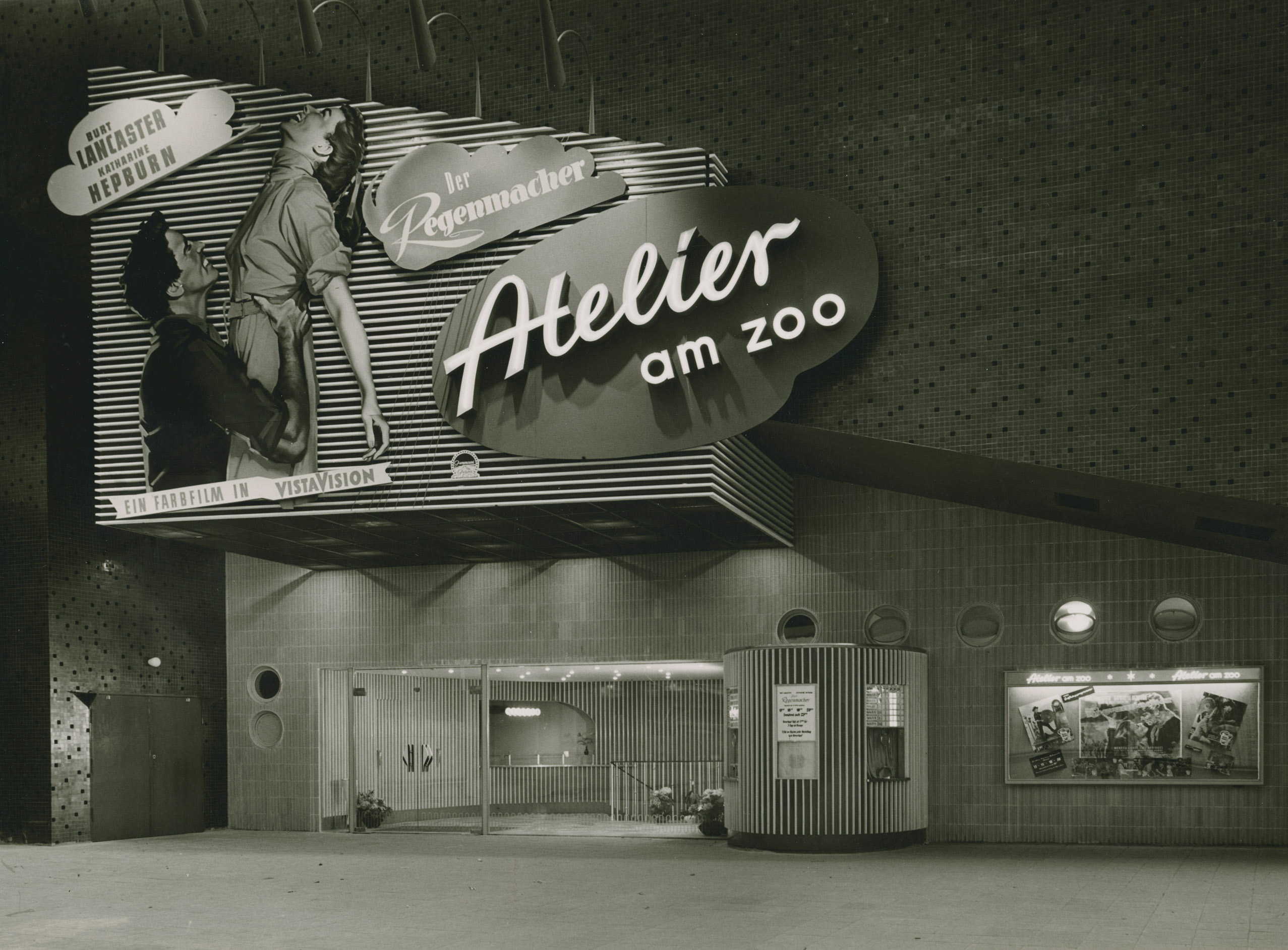 Black and white photo of the cinema façade with film advertisements