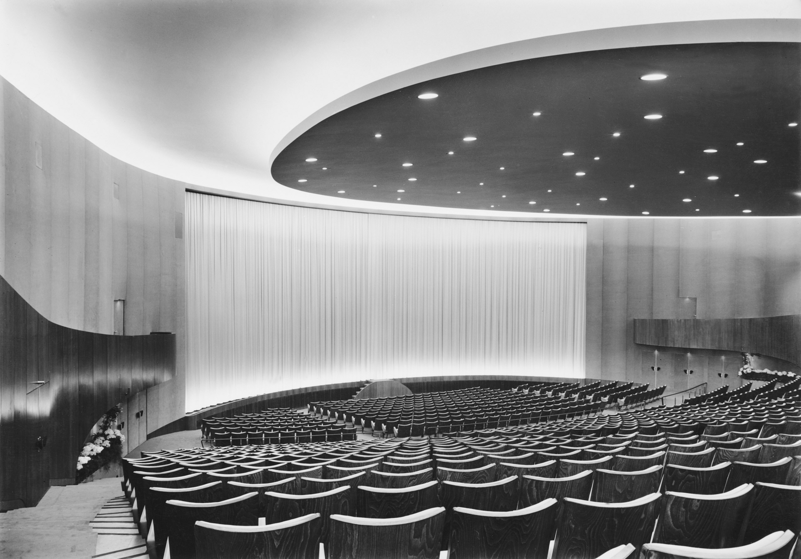Black and white photo: auditorium facing the screen