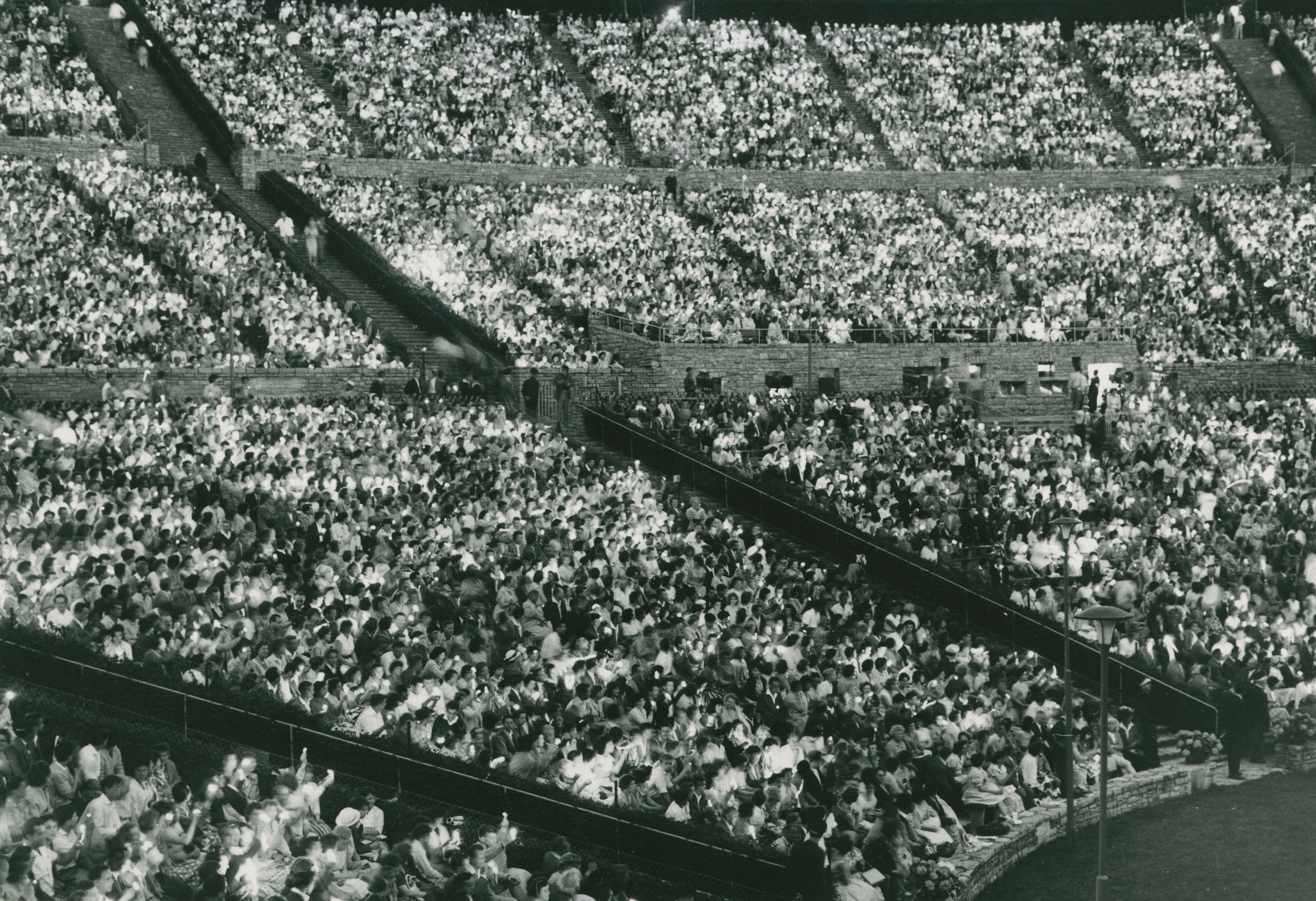 Black and white photo: rows of seats full of spectators