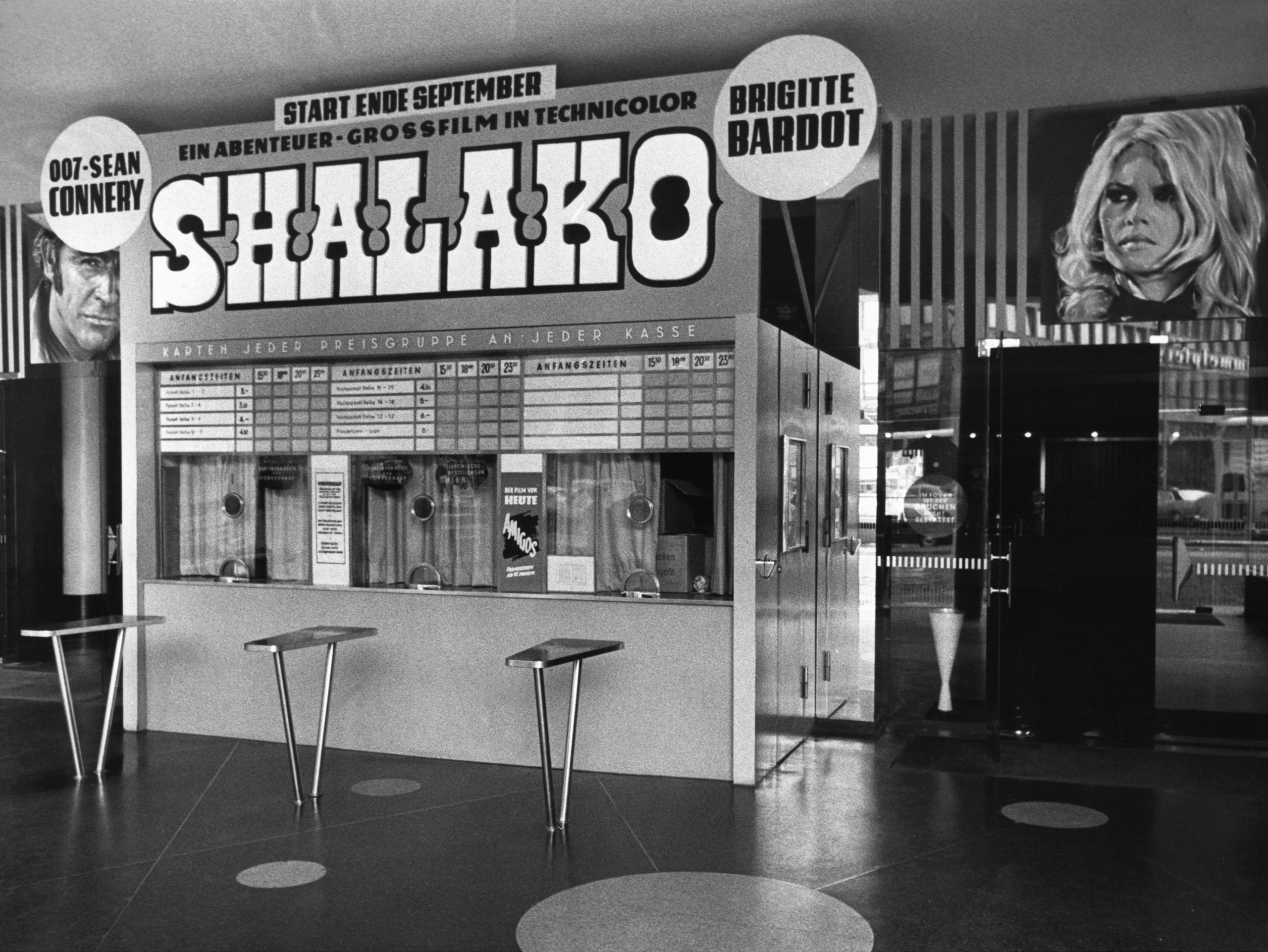 Black and white photo: box office in the entrance hall with film advertisements