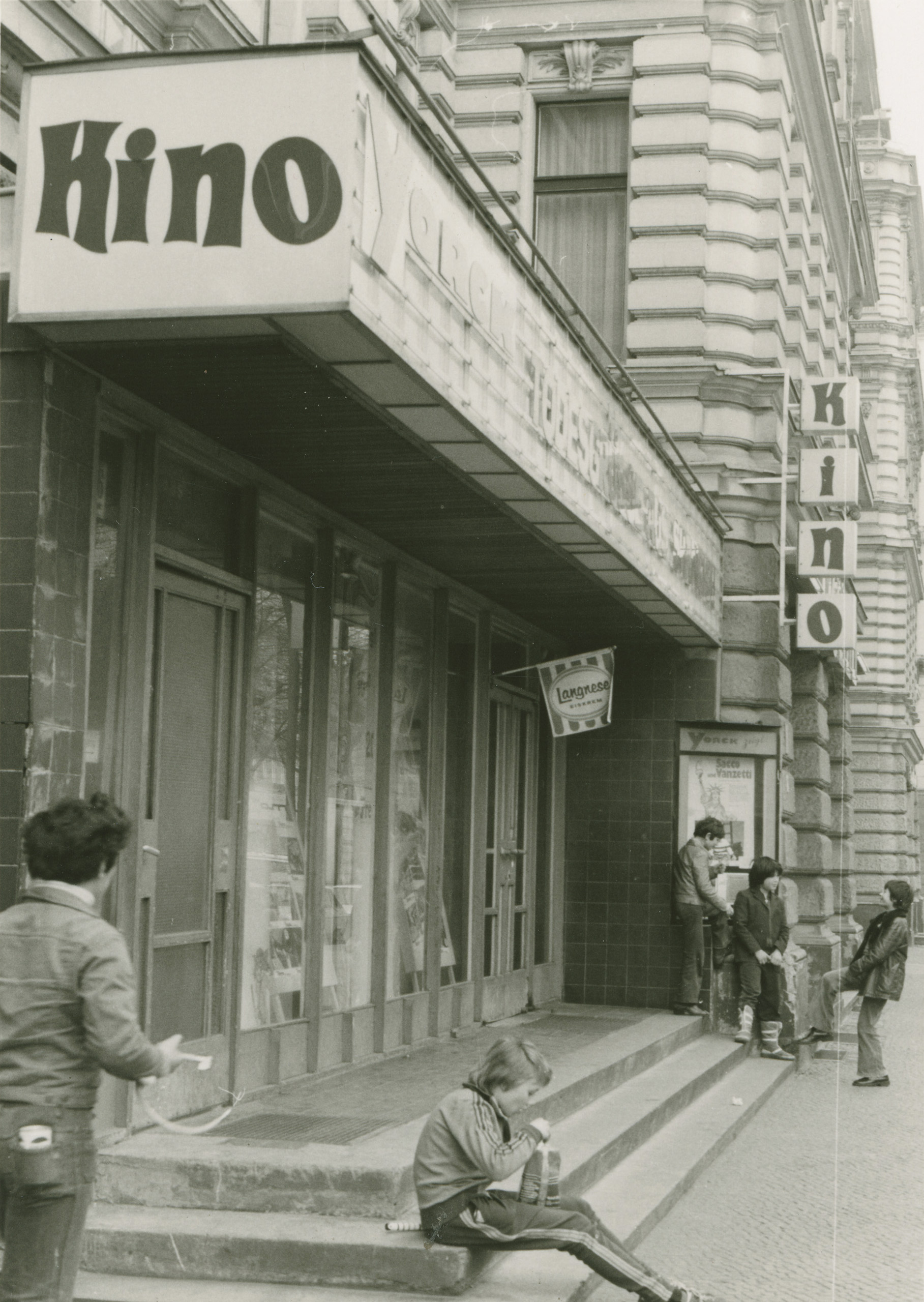 Black and white photo of youths outside the cinema