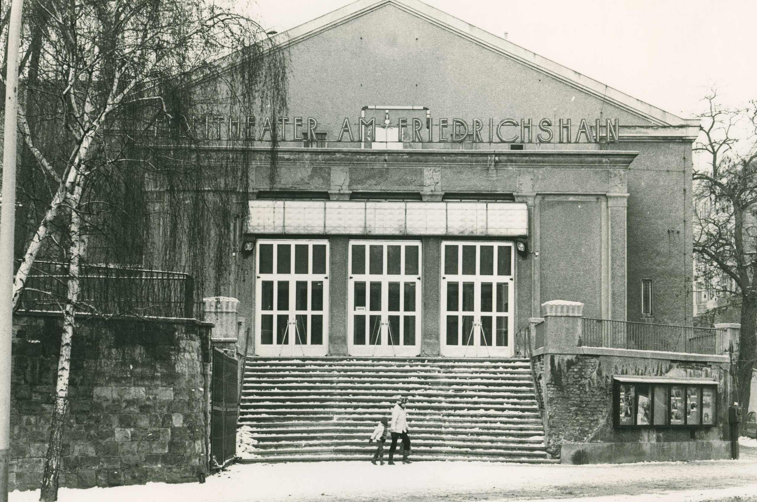 Black and white photo: cinema façade with passersby in winter