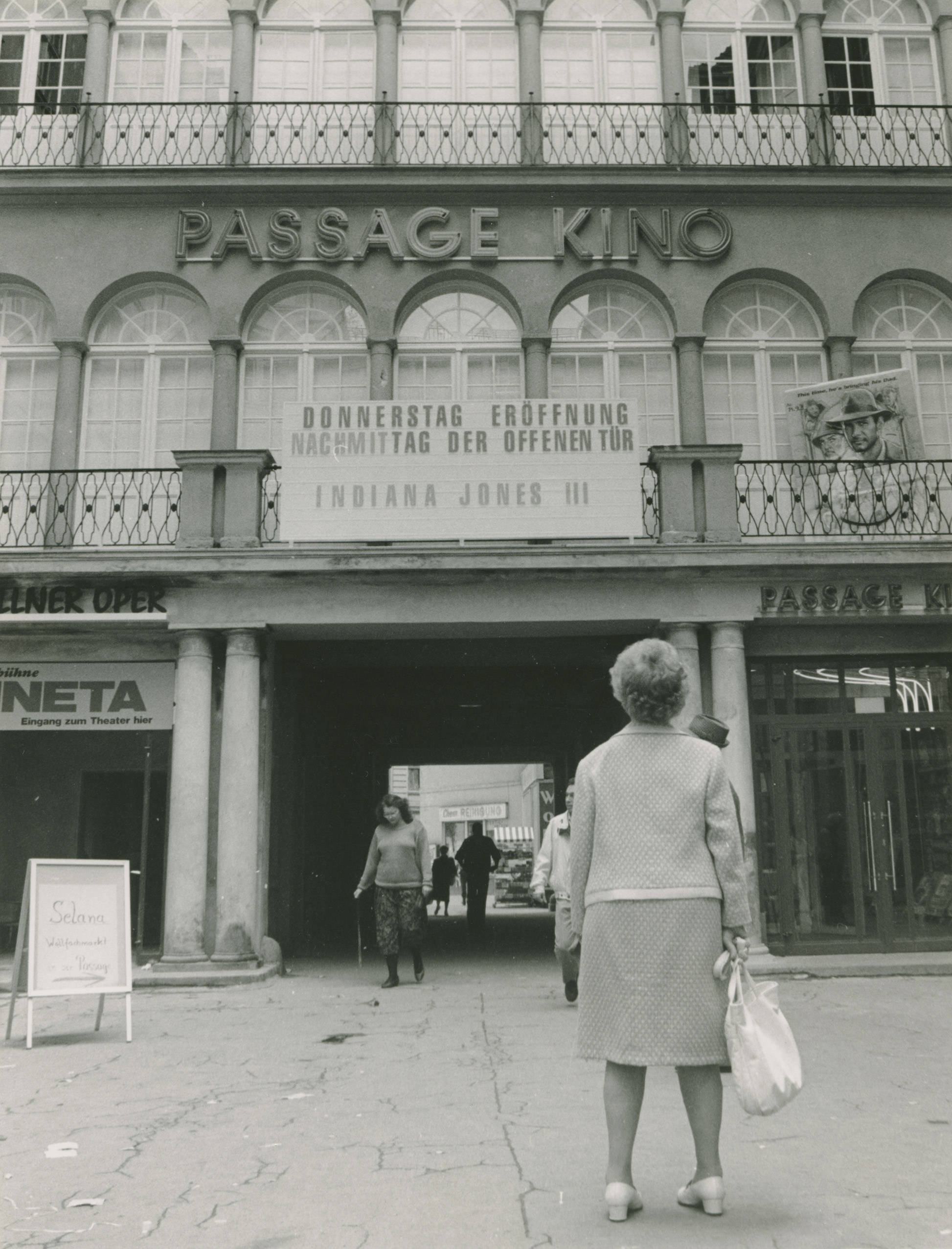 Black and white photo: driveway next to the entrance of the cinema with display panel and lettering
