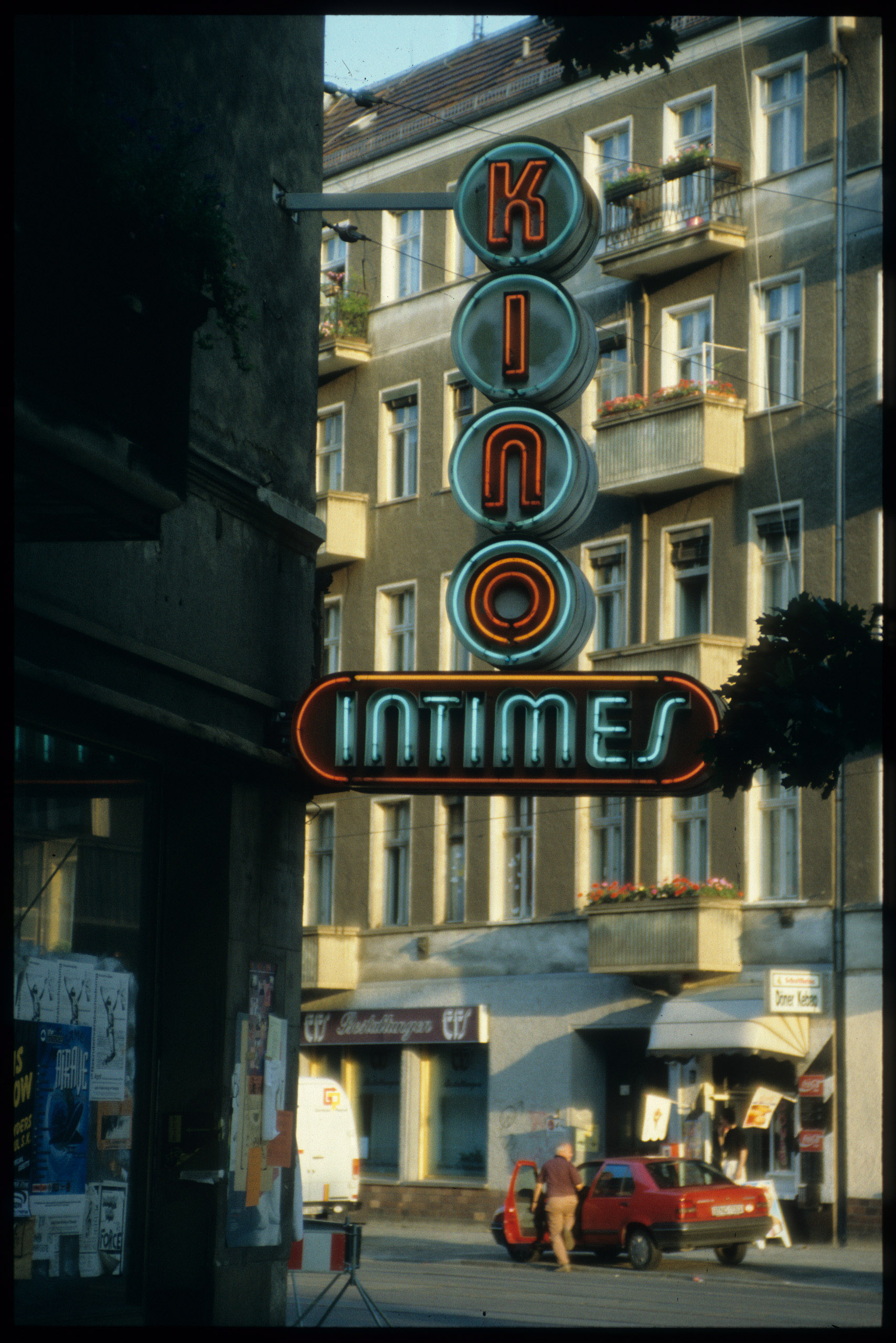 Color photo: illuminated red and blue lettering of the cinema