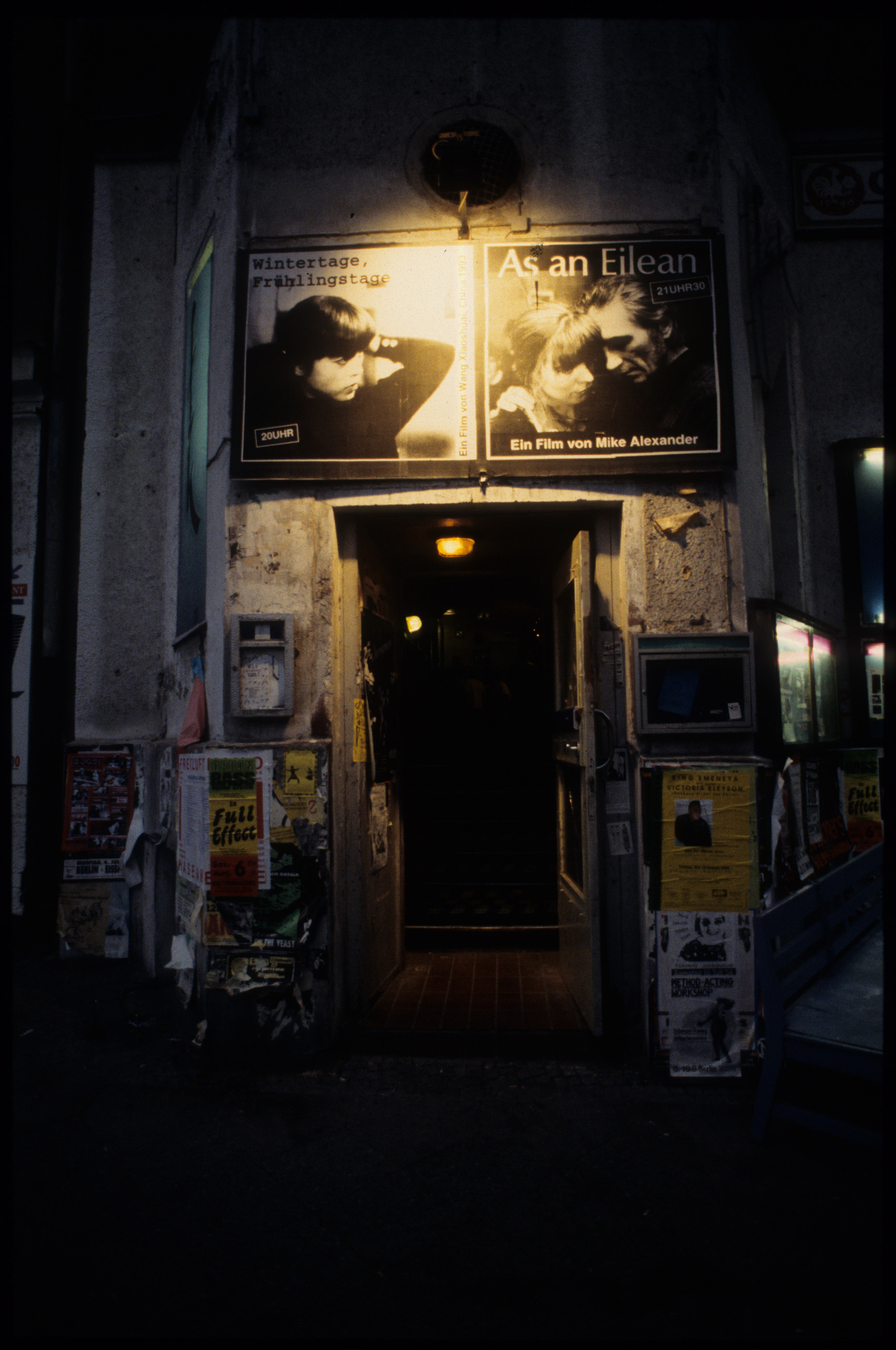 Color photo: barely lit entrance to the cinema with advertisements