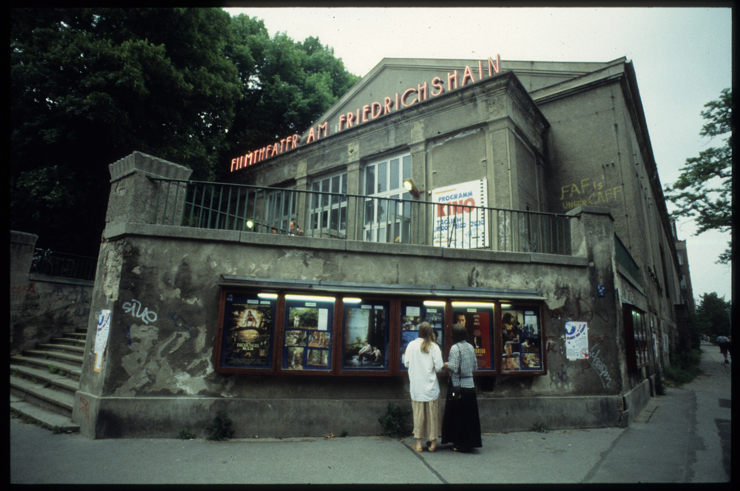 Color photo: cinema building with film posters in display cases and illuminated advertisements