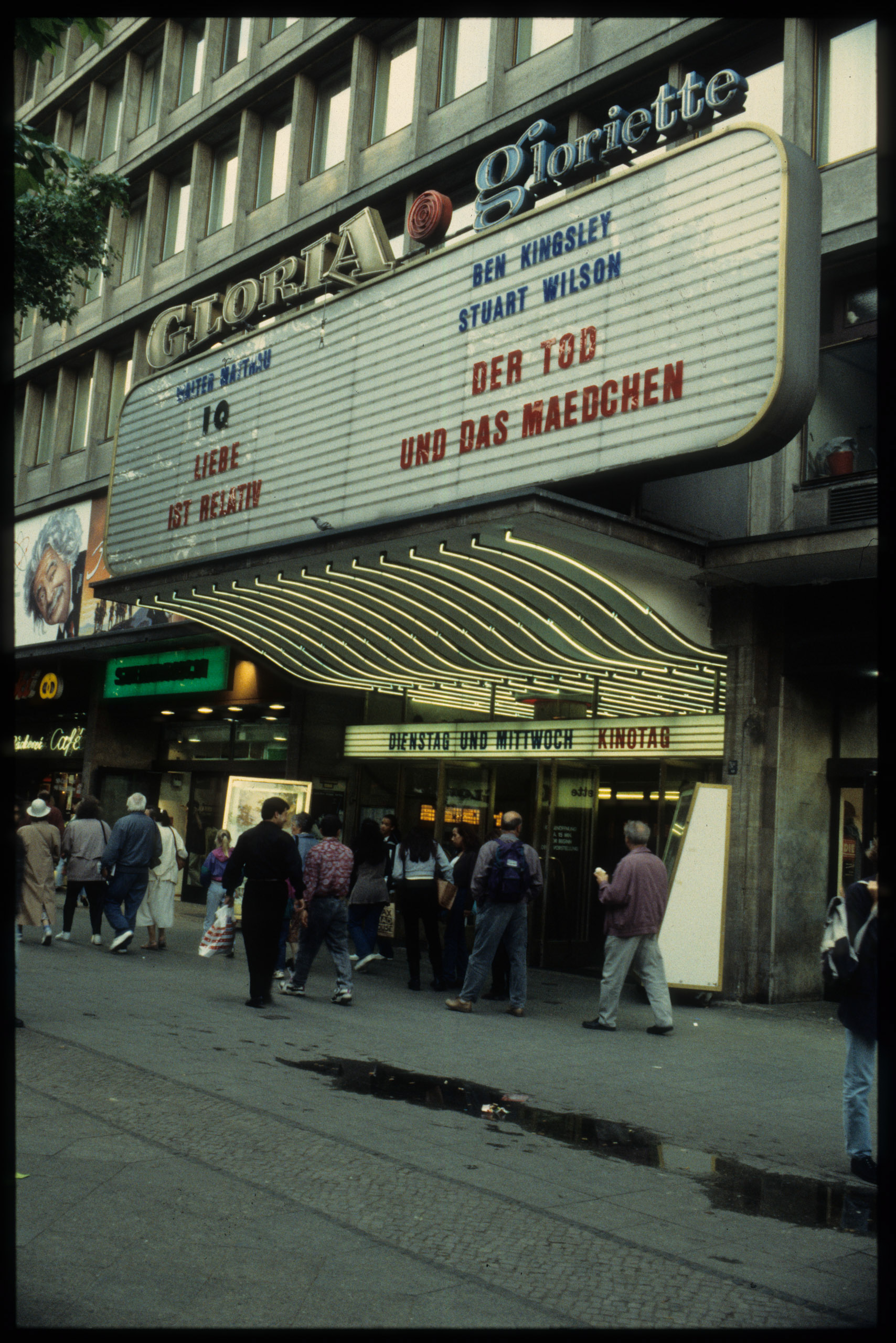 Color photo: passersby in front of the entrance with illuminated advertisements and display panel