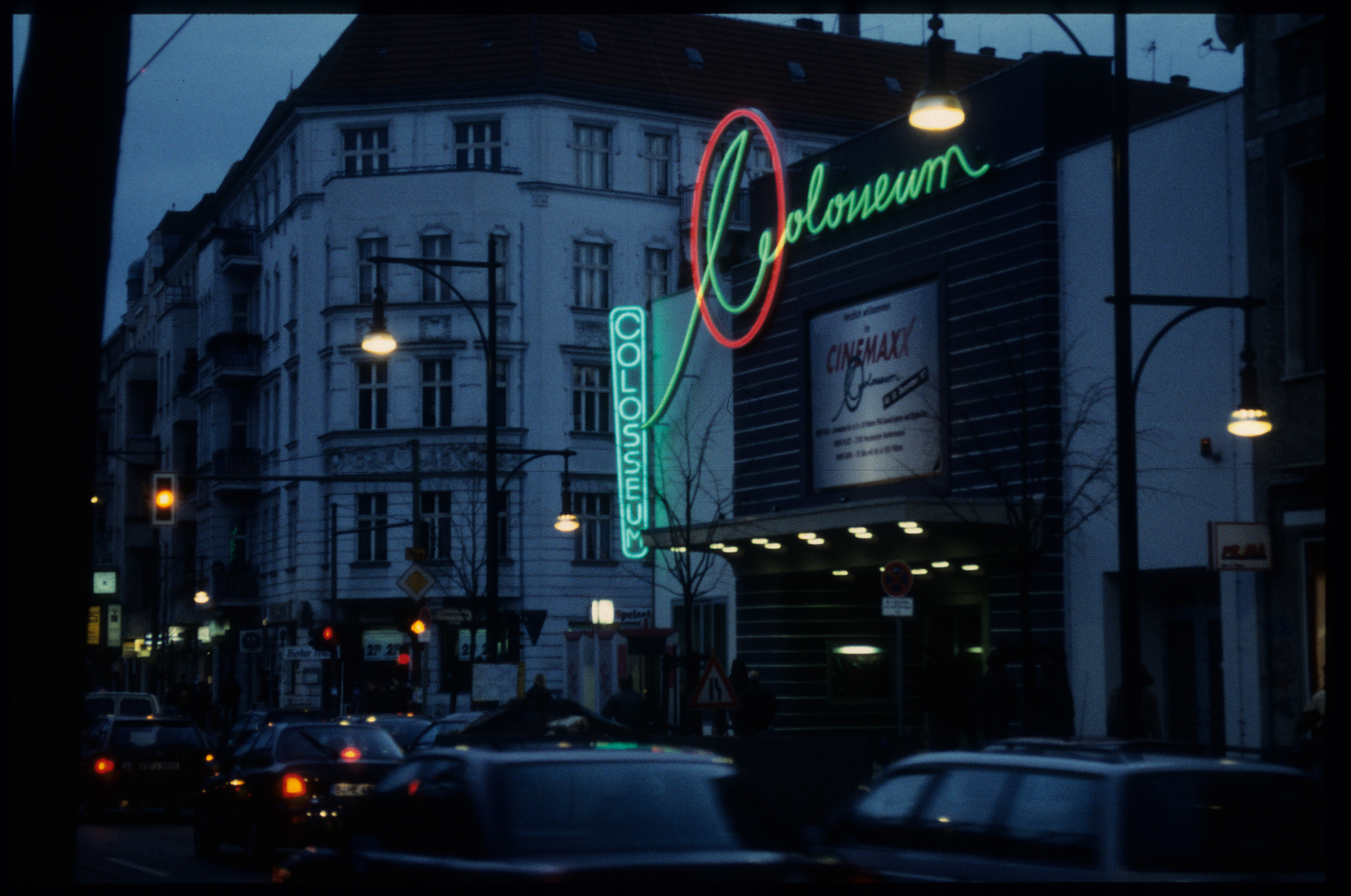 Color photo: façade at night with illuminated lettering