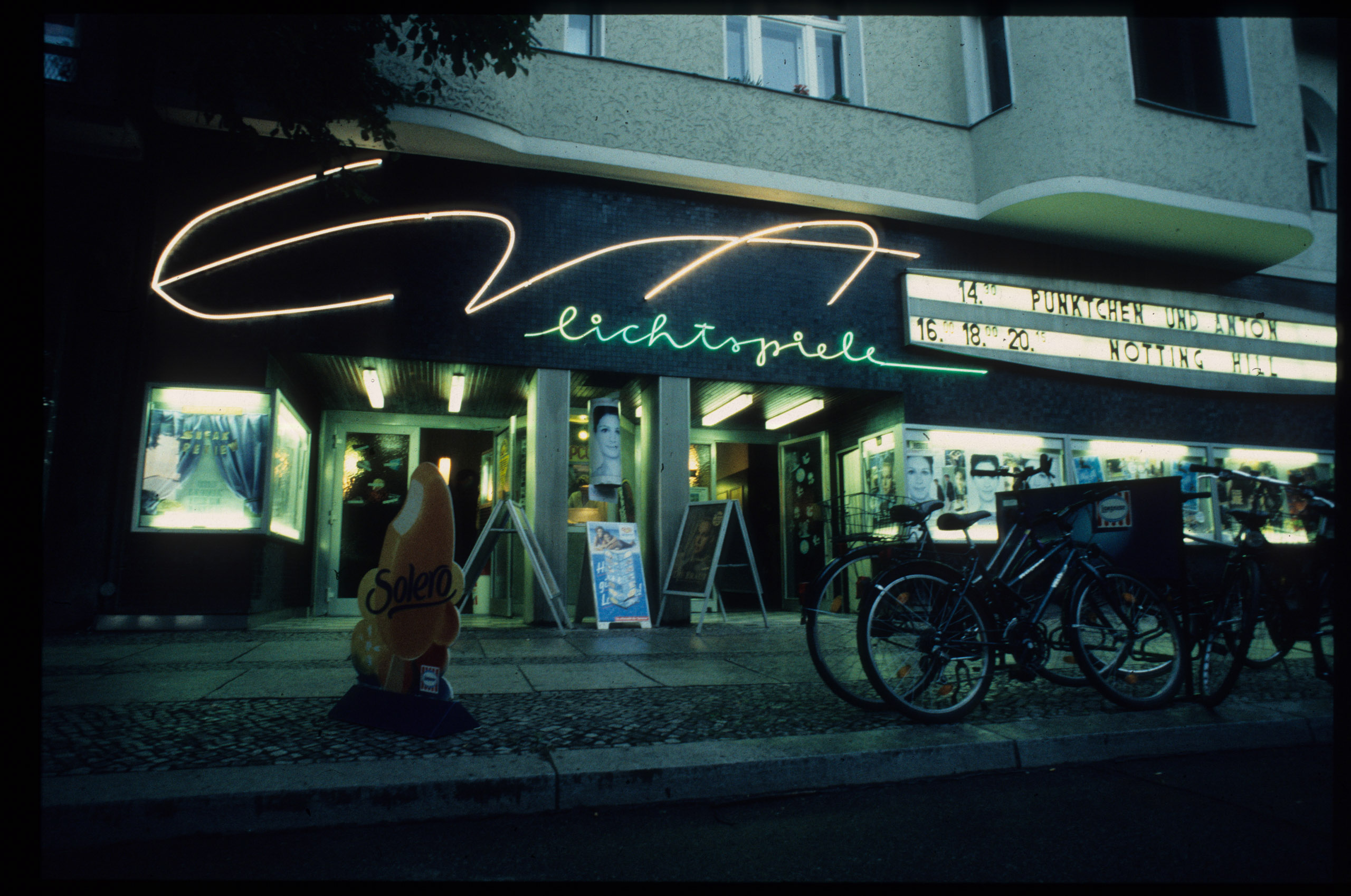 Color photo: façade at night with illuminated lettering and display panel
