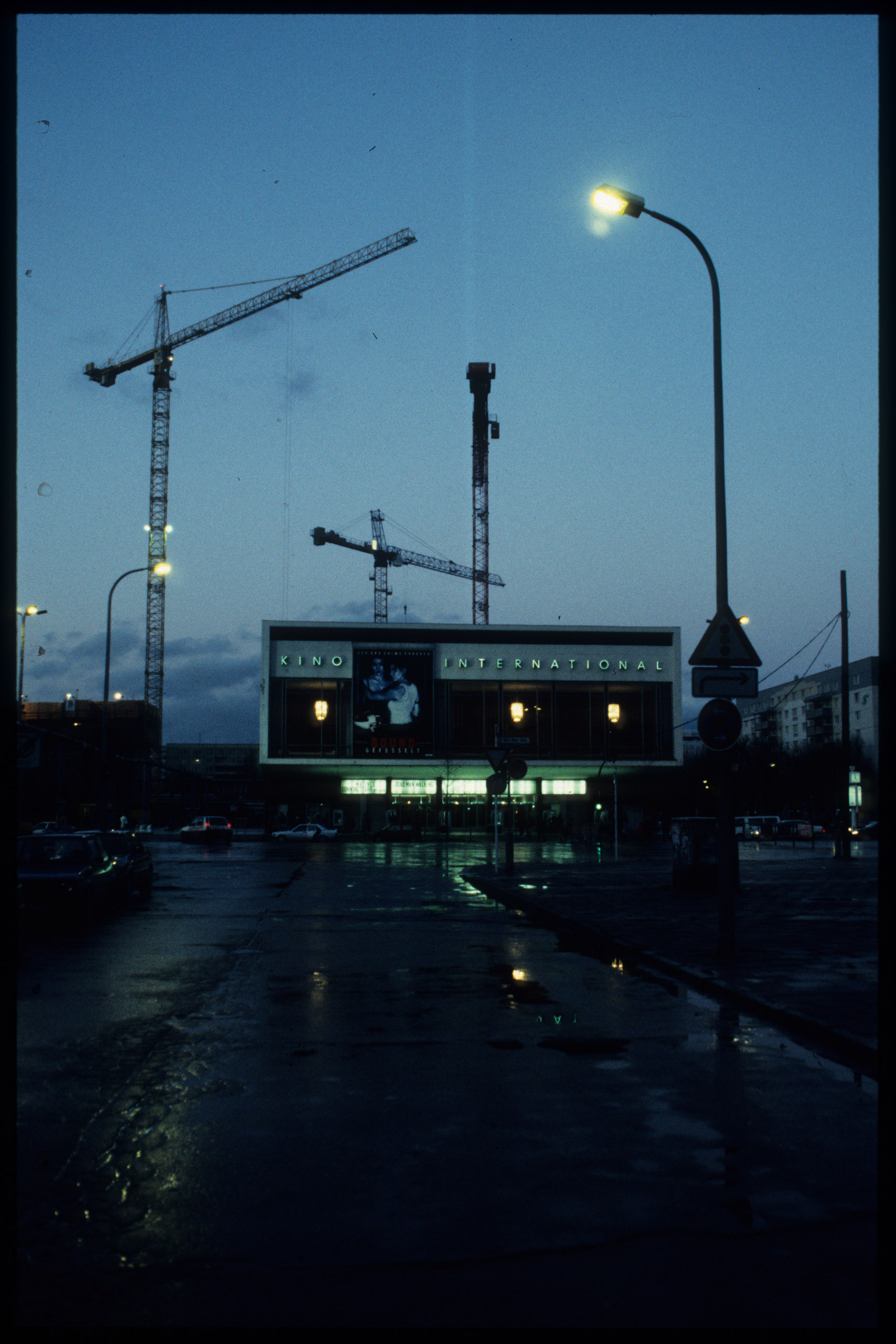 Color photo: panorama of the cinema with silhouettes of constructions cranes in the background