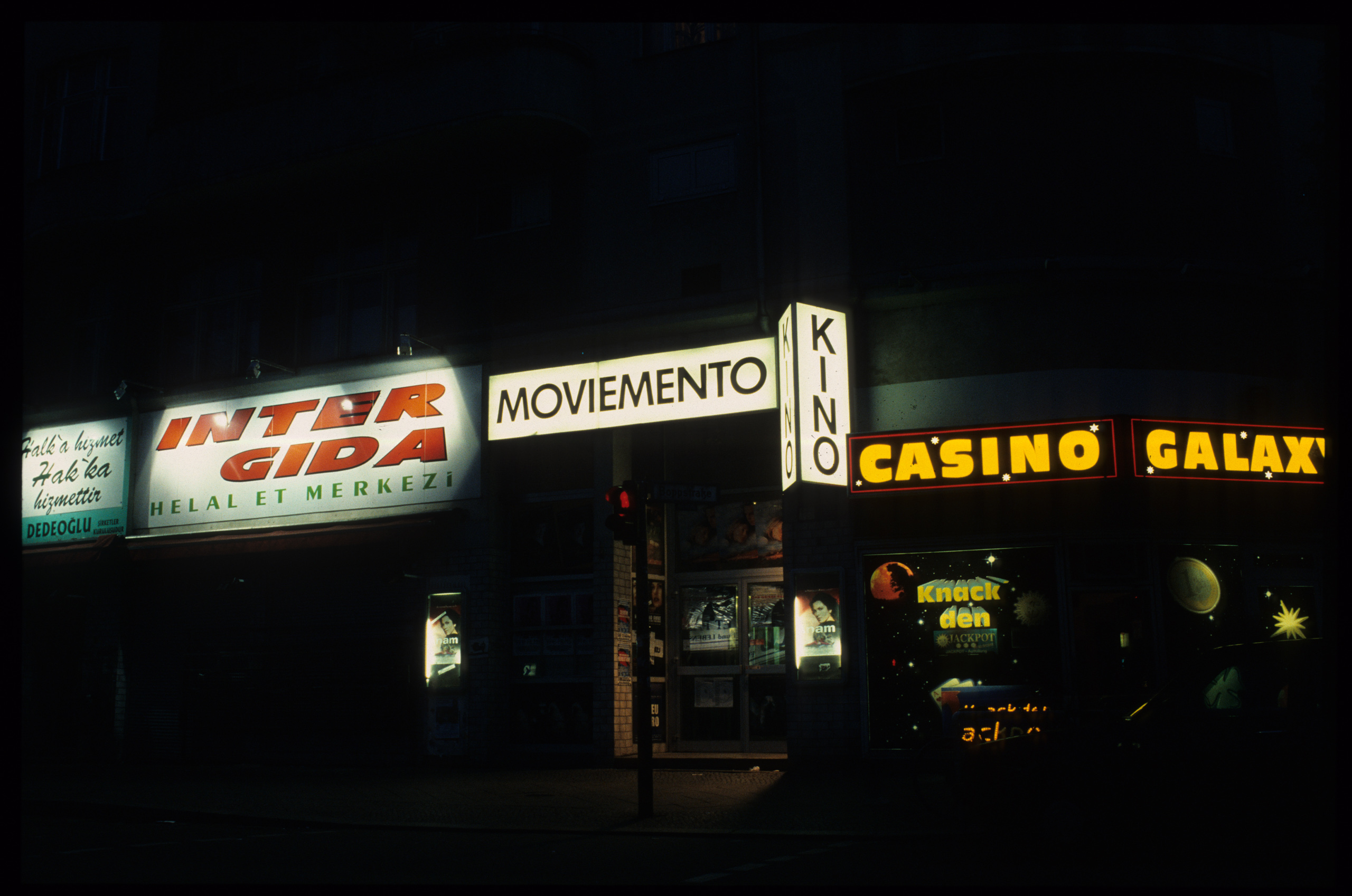 Color photo: façade at night with illuminated advertisements