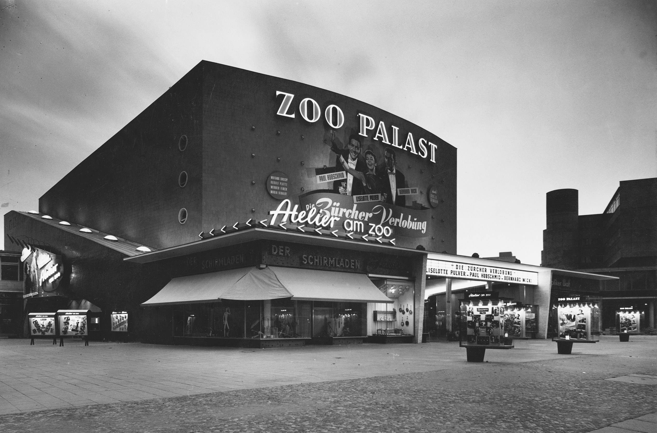 Black and white photo: façade with illuminated advertisements and film posters at night
