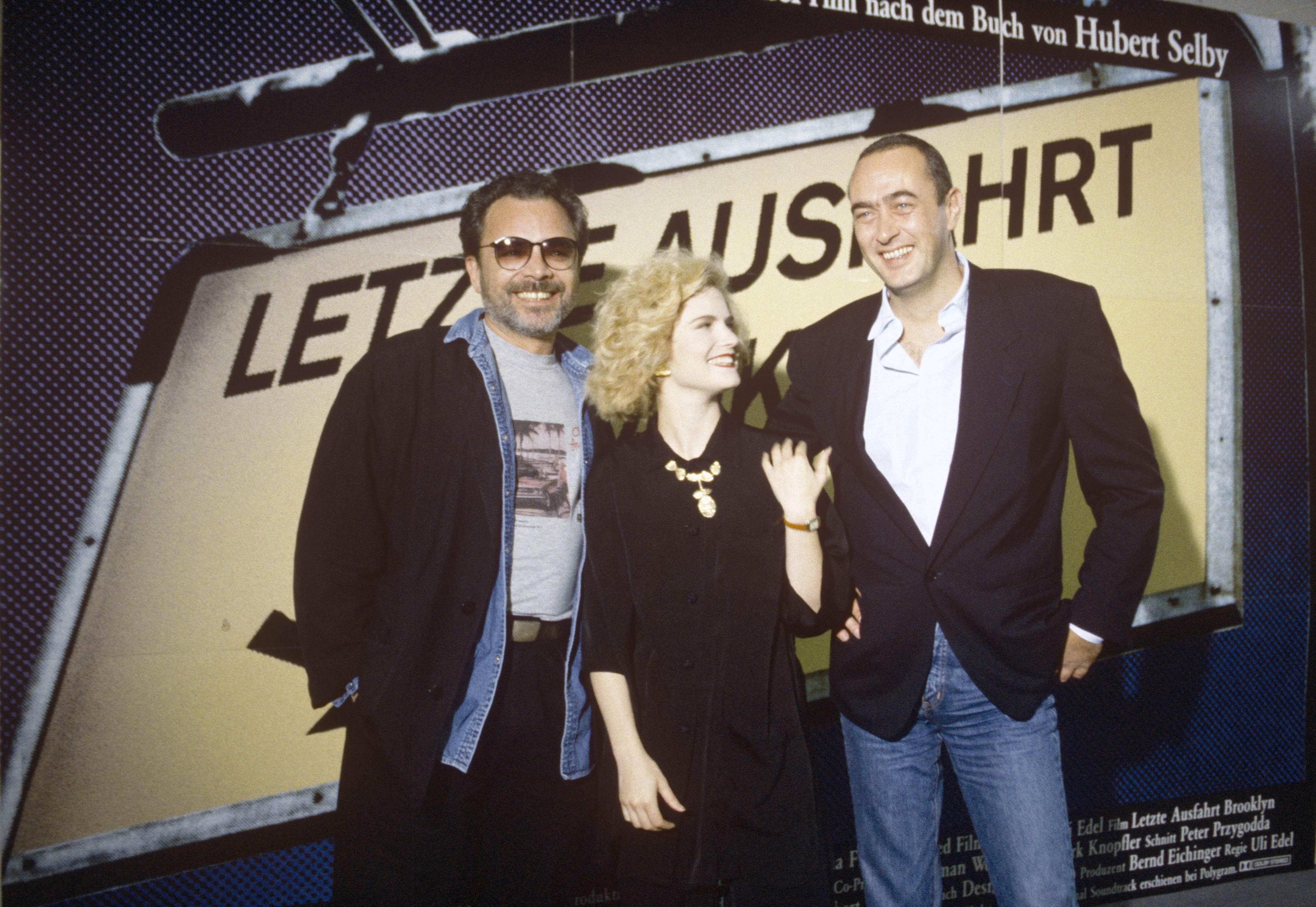 Foto von Uli Edel, Jennifer Jason Leigh und Bernd Eichinger bei der Premiere des Films Last Exit to Brooklyn (Bundesrepublik Deutschland/Vereinigte Staaten von Amerika 1989, Regie: Uli Edel)
