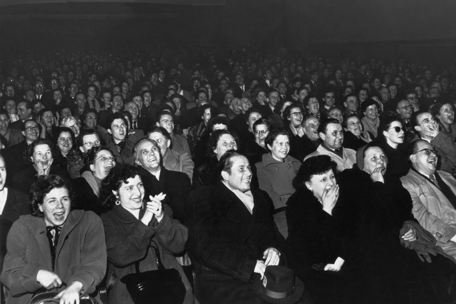 Black and white photo of cinema audience looking at the screen