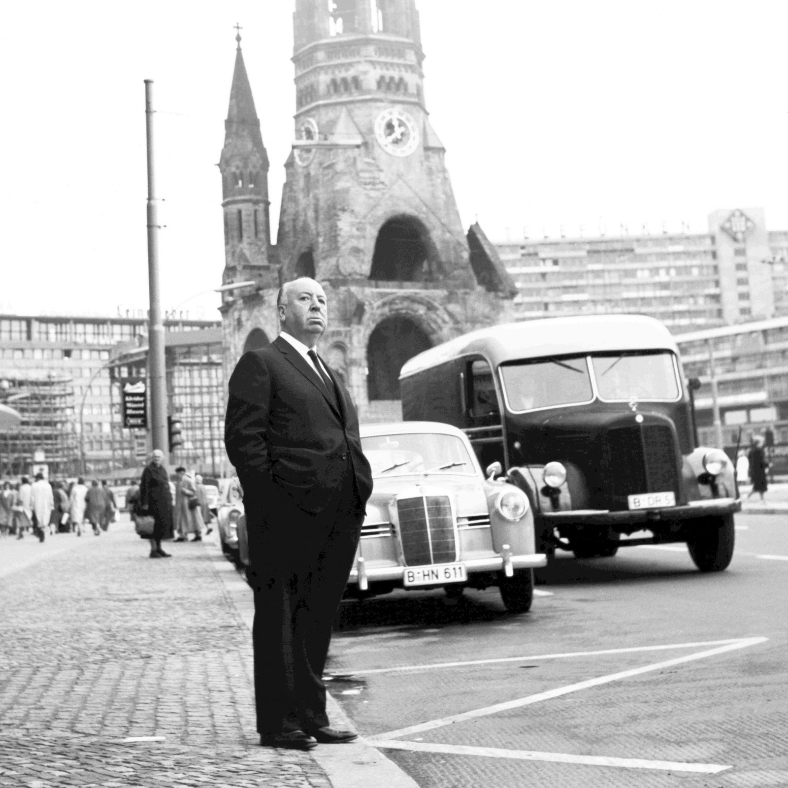 Black and white portrait of Alfred Hitchcock at Breitscheidplatz in Berlin with the Kaiser Wilhelm Memorial Church in the background