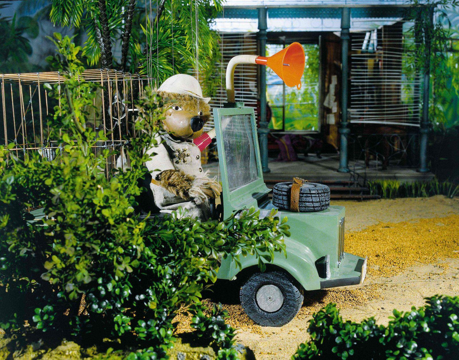 Still from Drei Dschungeldetektive: String puppet bear in a car behind a green bush