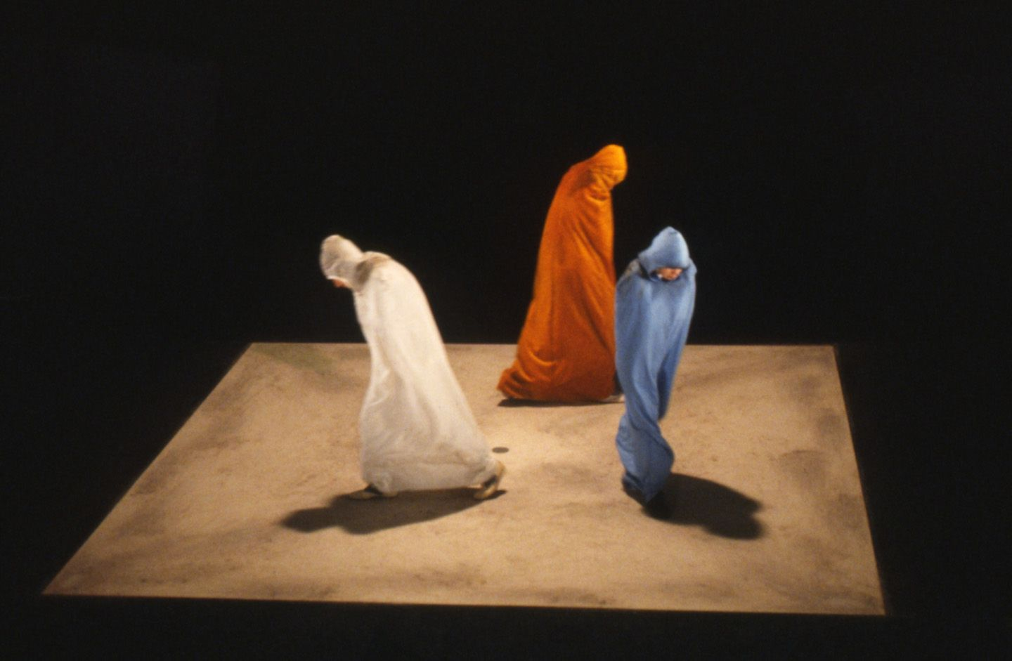 Colour photo: Still from television series Quadrat I, three figures dressed in respectively blue, red and yellow capes walk within a brown square on the ground