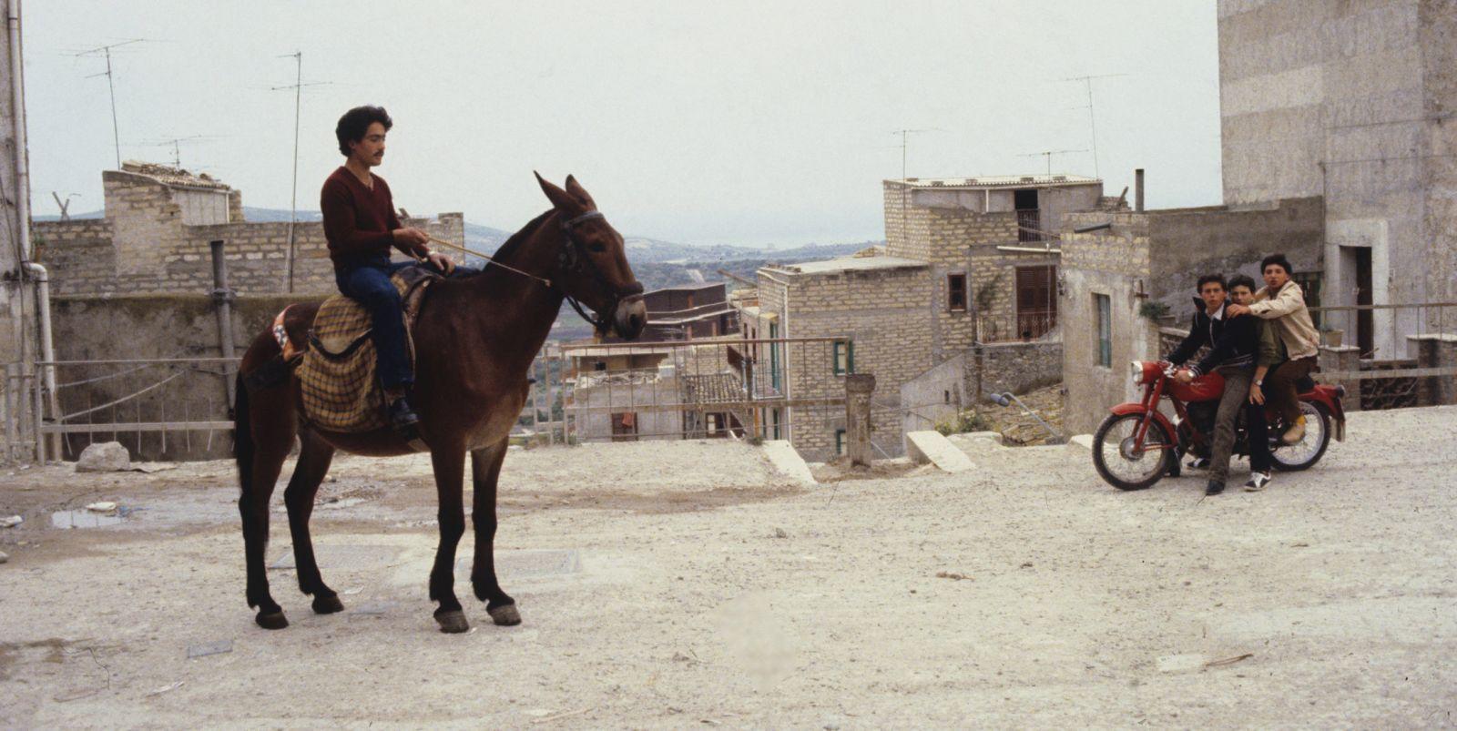 Farbiges Szenenfoto: Ein Mann sitzt auf einem Pferd, im Hintergrund eine heruntergekommene Stadt