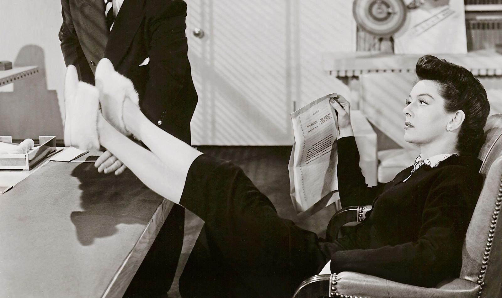 Schwarz-weiß-Szenenfoto: Frau sitzt am Schreibtisch, die Füße mit puscheligen Schuhen lässig auf den Tisch gelegt