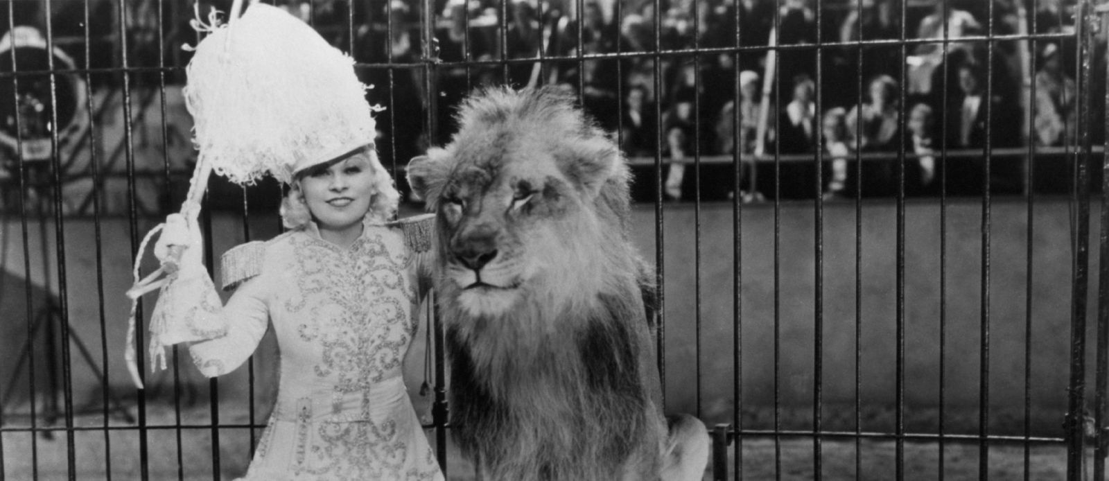 Black and white still of Mae West and a lion