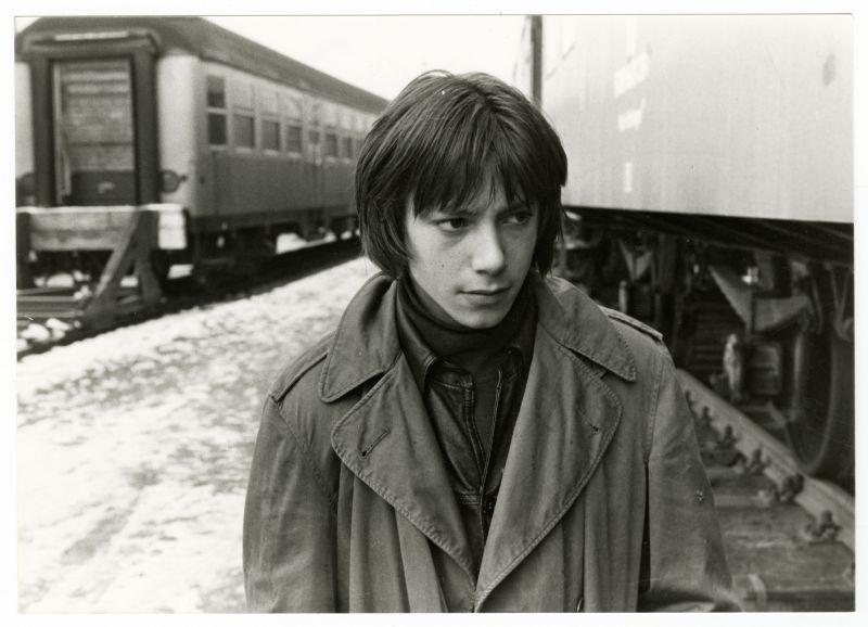 Schwarz-weiß-Szenenfoto: Junger Mann mit ernstem Gesicht am Bahnhof