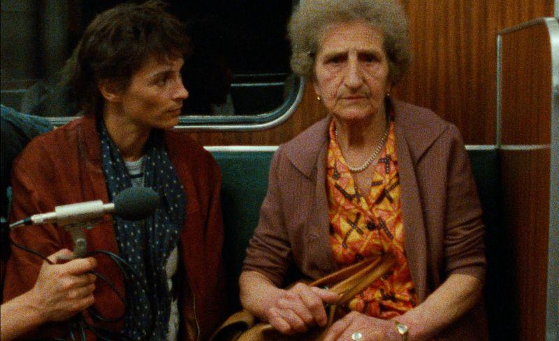 Die Regisseruin sitzt mit einer älteren Frau in der U-Bahn-Linie 8